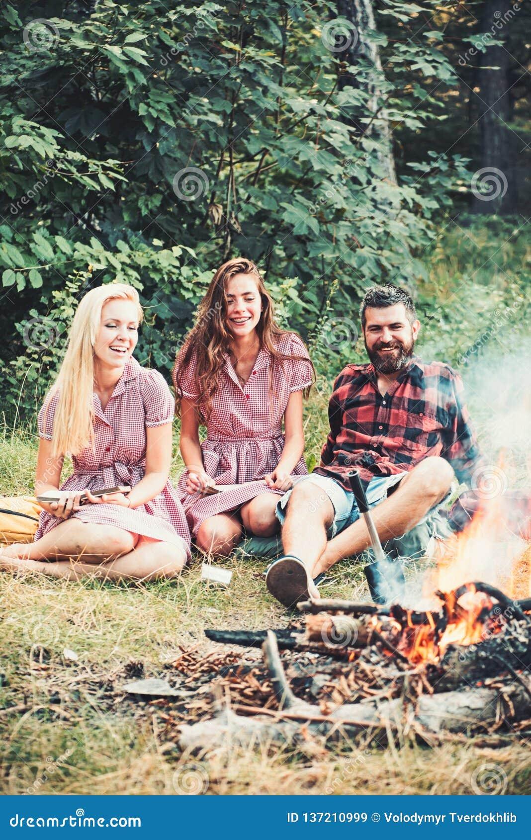Glückliche Freunde am Lagerfeuer Bärtiger Mann und Frauen lächeln am Feuer Hippie in palid Hemd und Mädchen in den Weinlesekleide