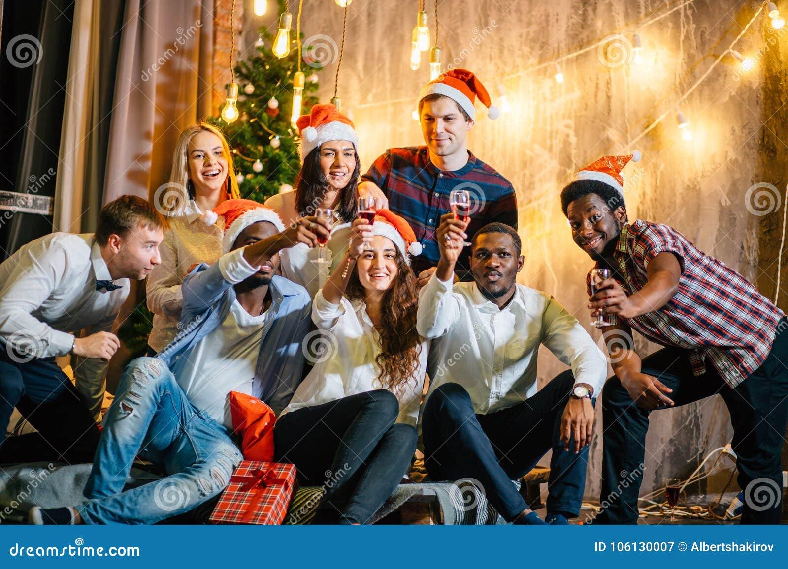Glückliche Freunde mit Champagner Weihnachten feiernd