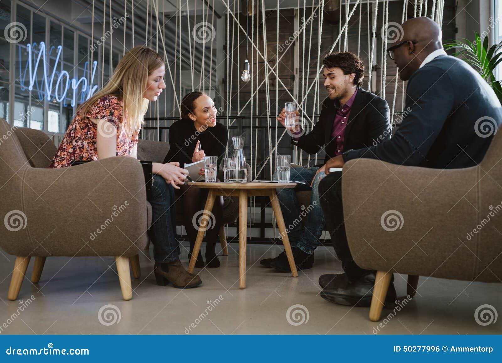 Glückliche gemischtrassige Geschäftsleute in der Sitzung