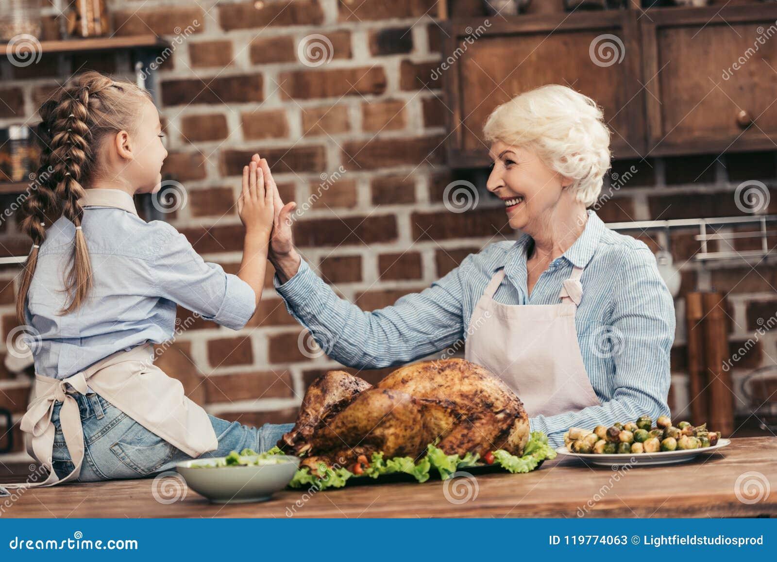 Glückliche Großmutter und Enkelin, die Hoch fünf auf Danksagung nach erfolgreichem gibt