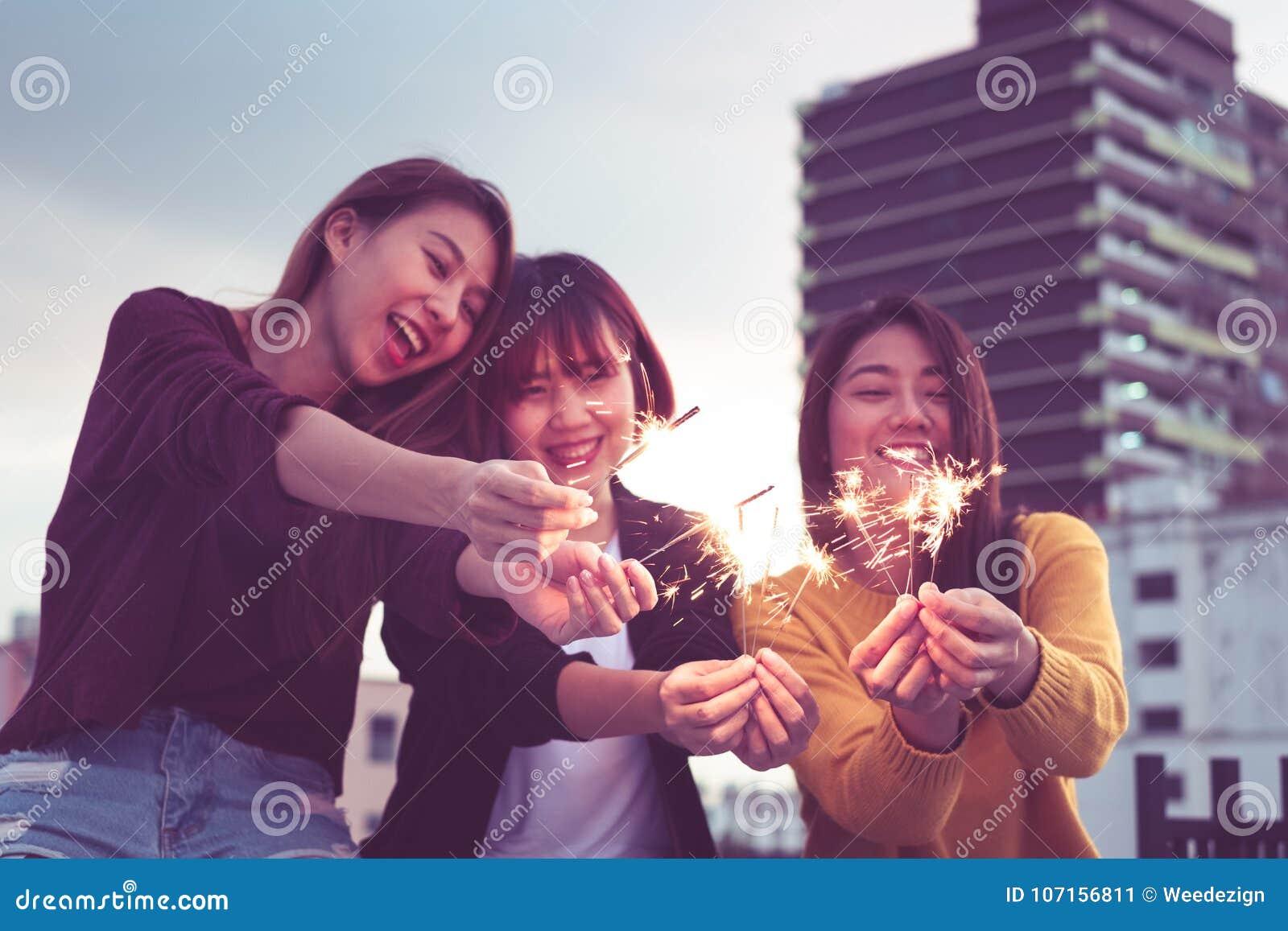 Glückliche Gruppe Asien-Freundinnen genießen und spielen Wunderkerze am Dach
