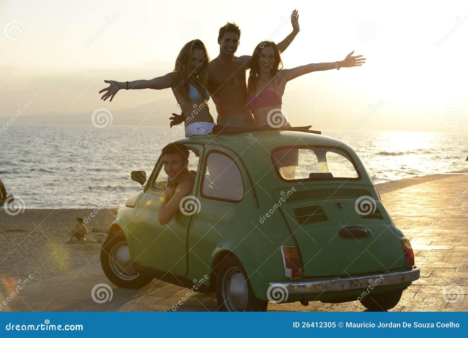 Glückliche Gruppe Freunde mit kleinem Auto auf Strand