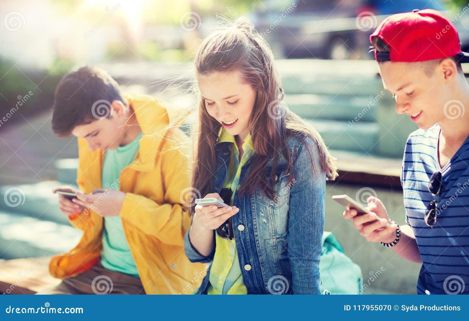Glückliche Jugendfreunde mit Smartphones draußen