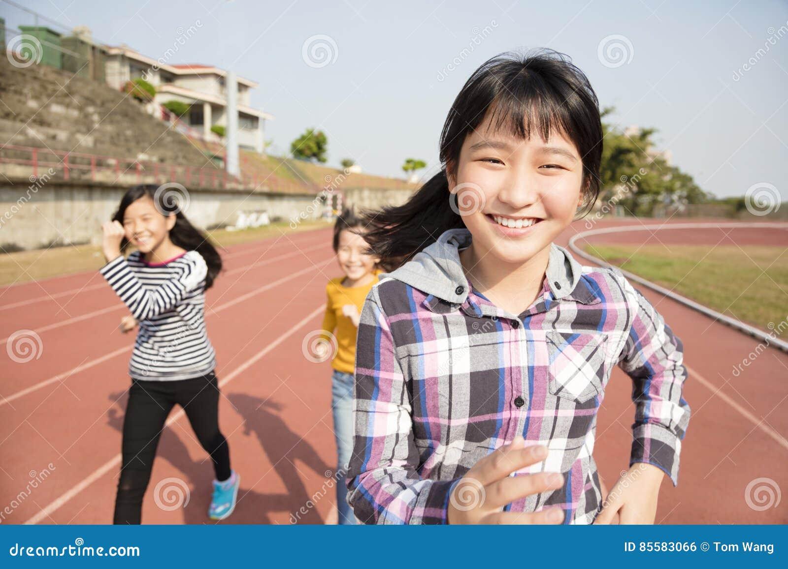 Glückliche Jugendlichmädchen, die auf der Bahn laufen