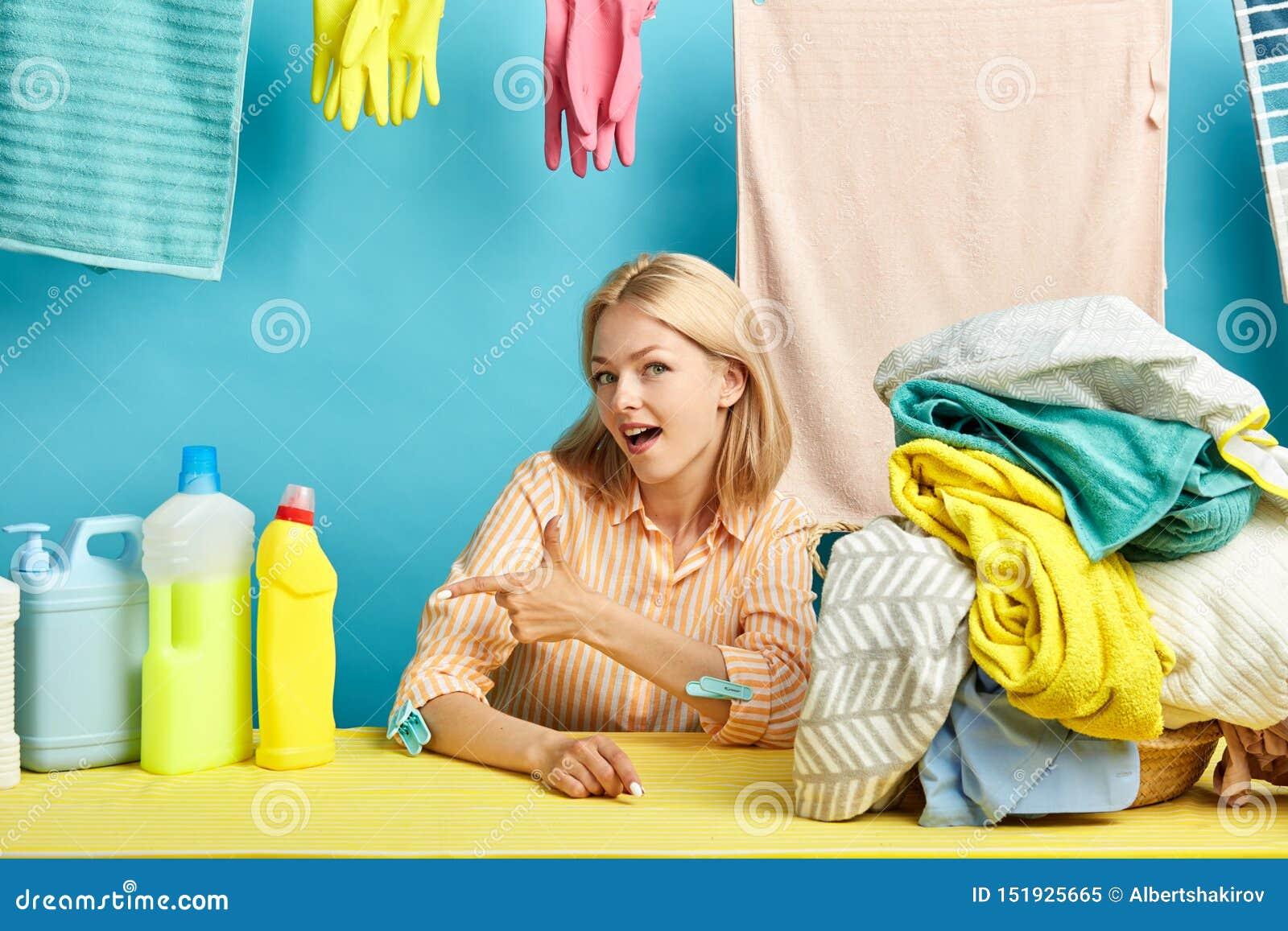 Glückliche junge Blondine, die auf flüssige Flasche des Abwasches zeigen