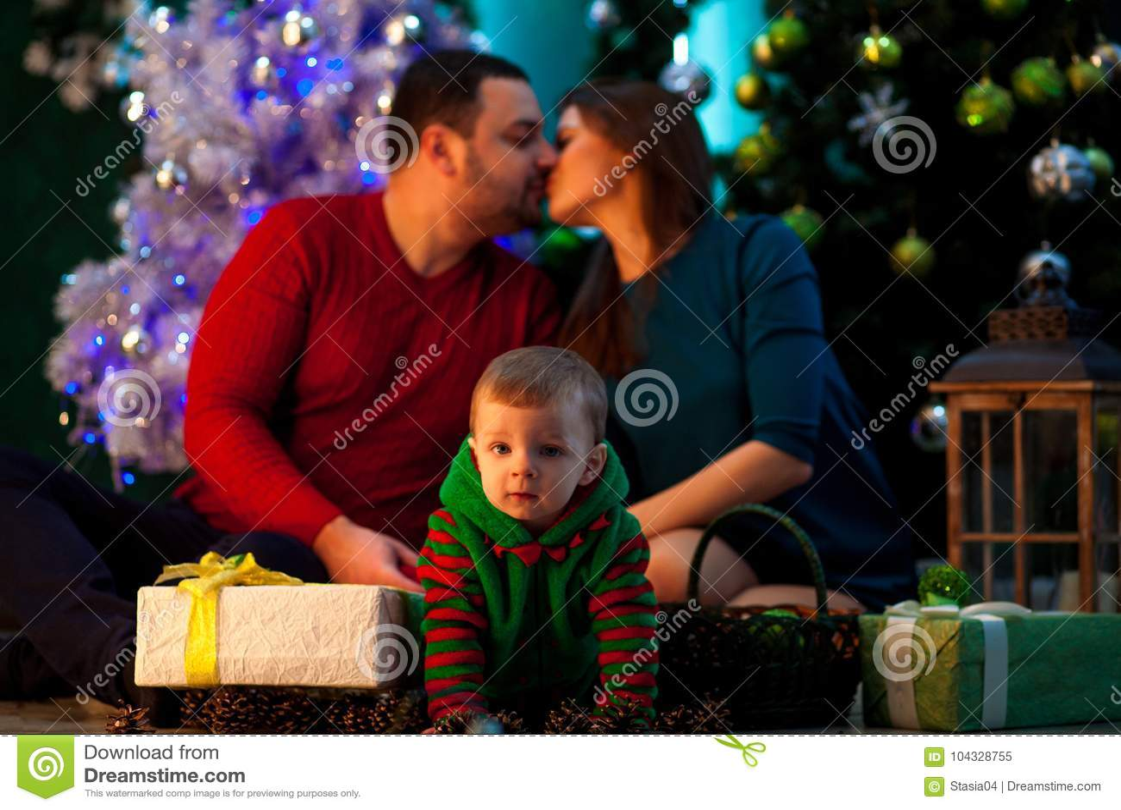 Glückliche junge Eltern küssen und ihr kleiner Sohn kriecht nahe Christus