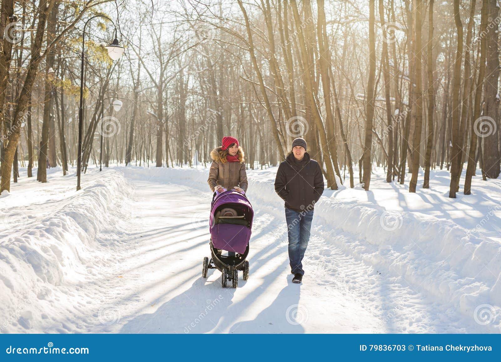 Glückliche junge Familie, die in den Park im Winter geht Die Eltern tragen das Baby in einem Spaziergänger durch den Schnee