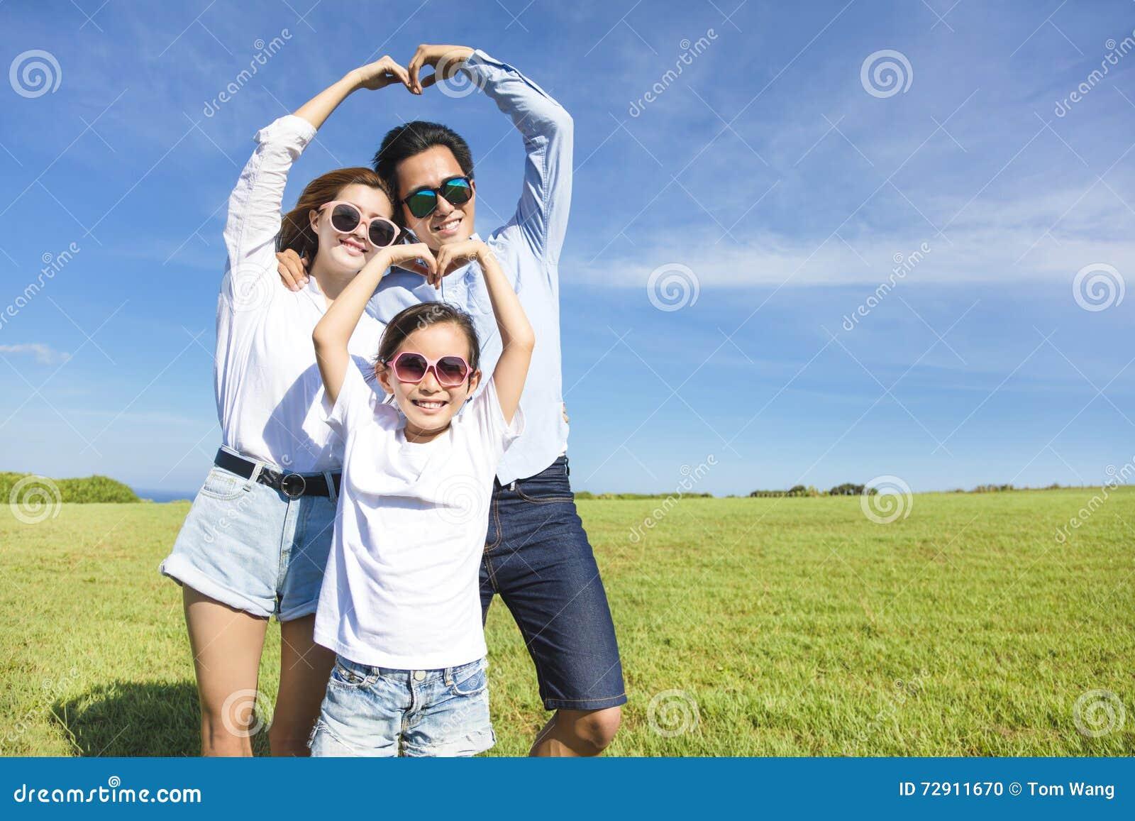 Glückliche junge Familie, die Liebesform bildet
