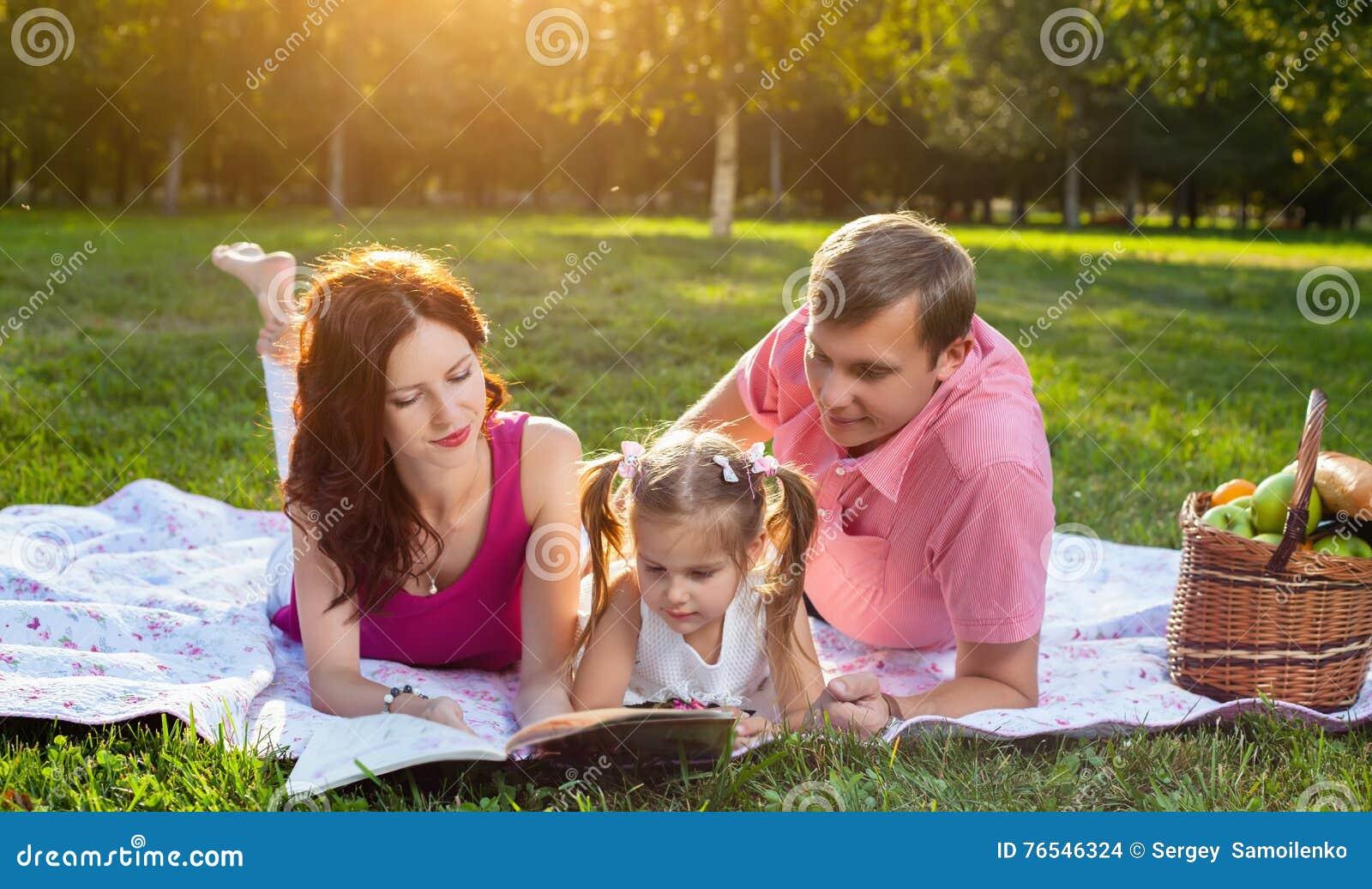Glückliche junge Familie, die Picknick an der Wiese hat