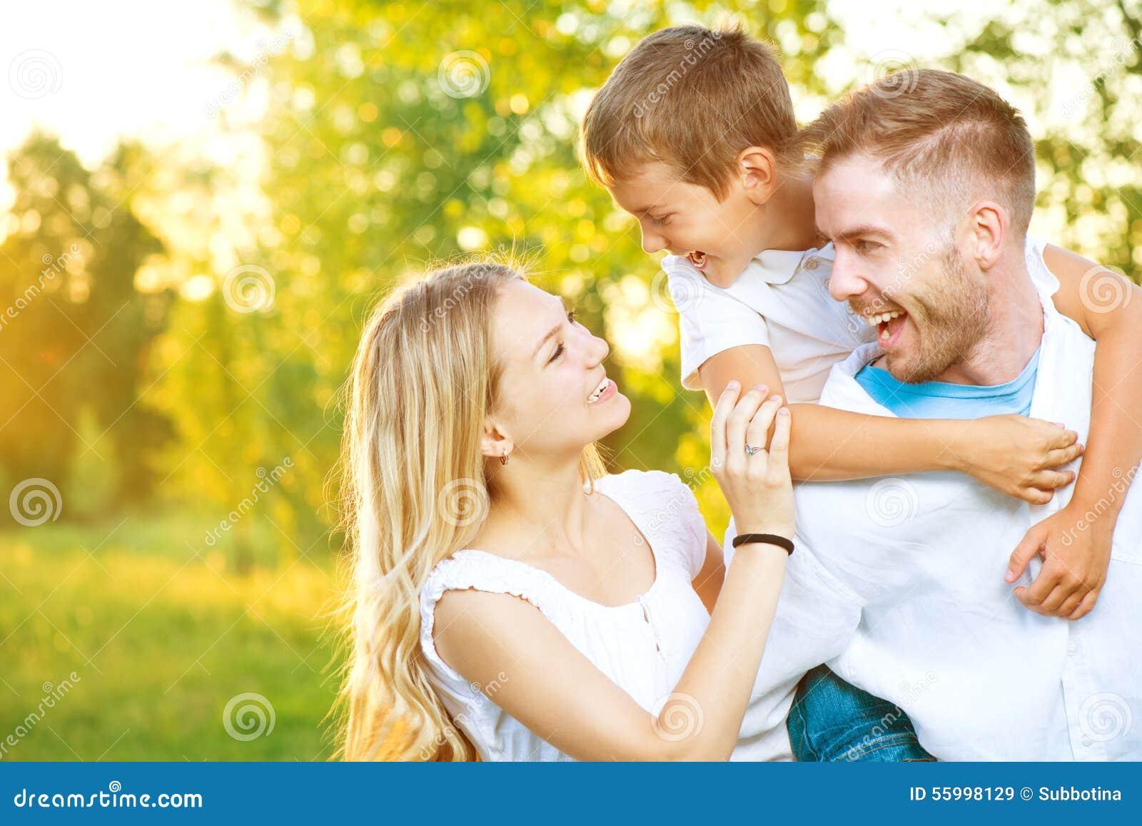Glückliche junge Familie, die Spaß draußen hat