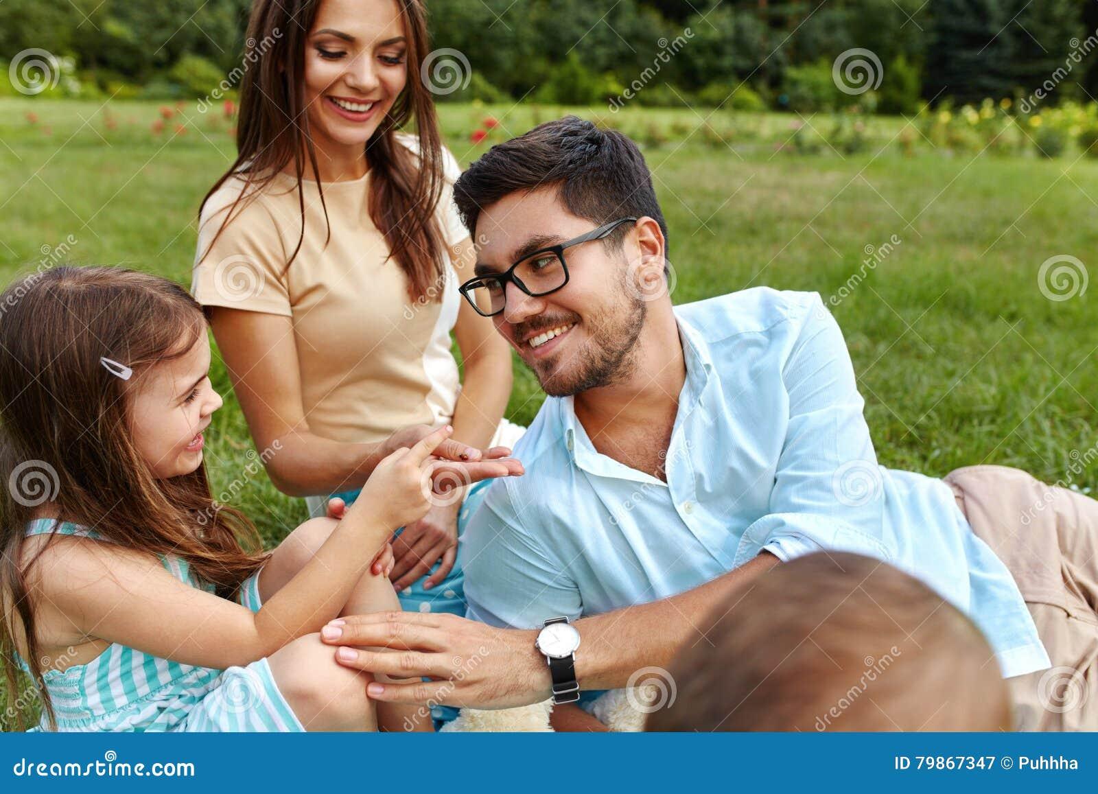 Glückliche junge Familie im Park Eltern und Kinder, die den Spaß, spielend haben