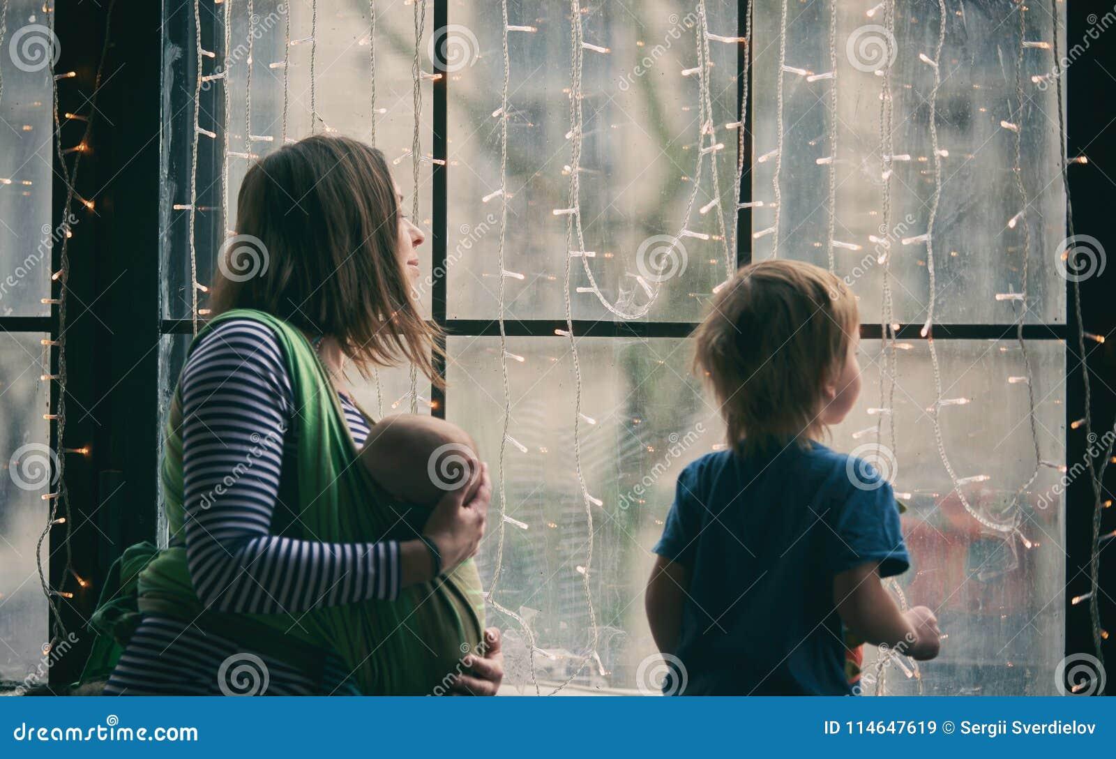 Glückliche junge Familie, schöne Mutter mit zwei Kindern, entzückender Vorschuljunge und Baby im Riemen schauen zusammen durch da