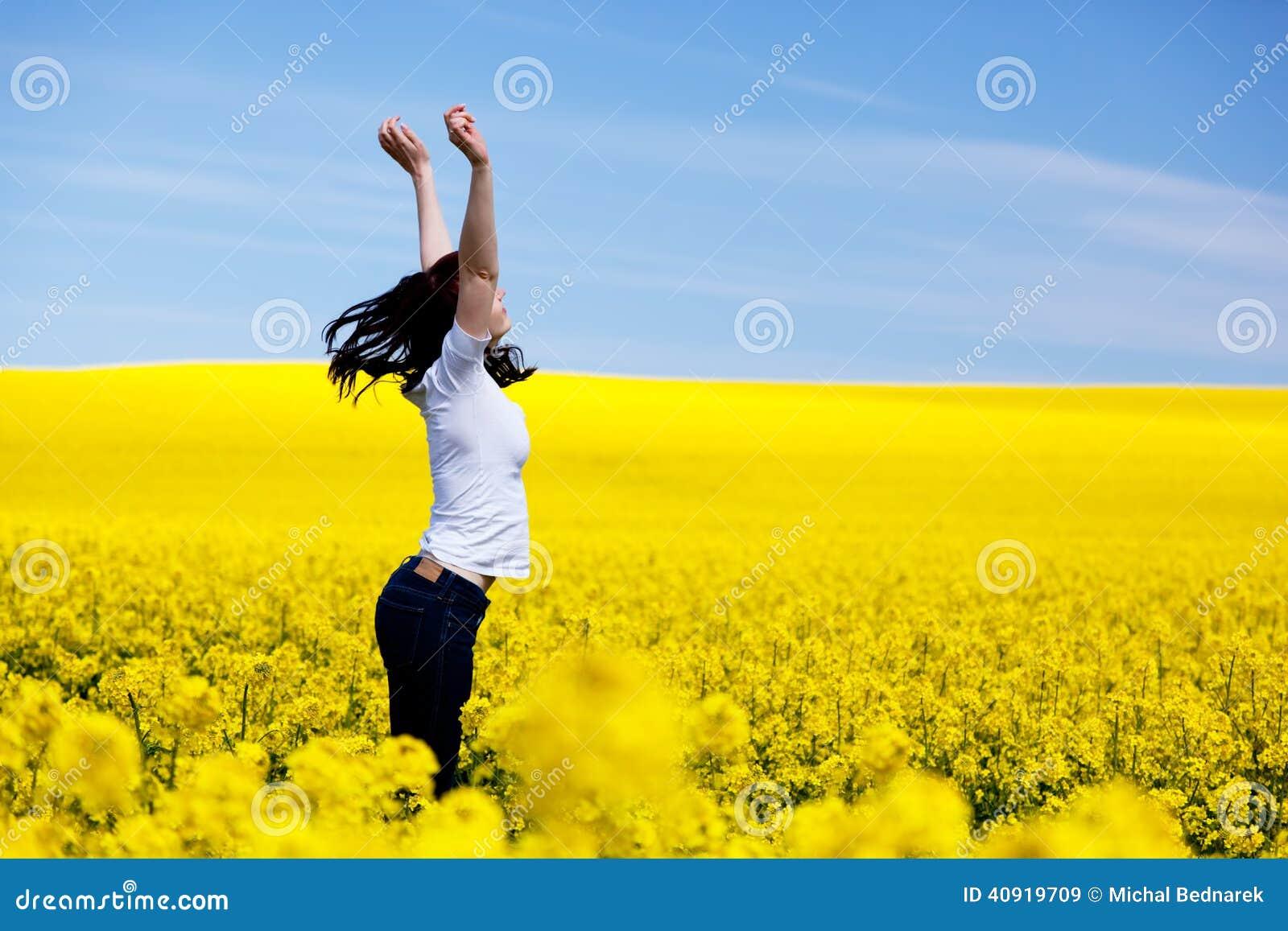 Glückliche junge Frau auf Frühlingsfeld Erfolg