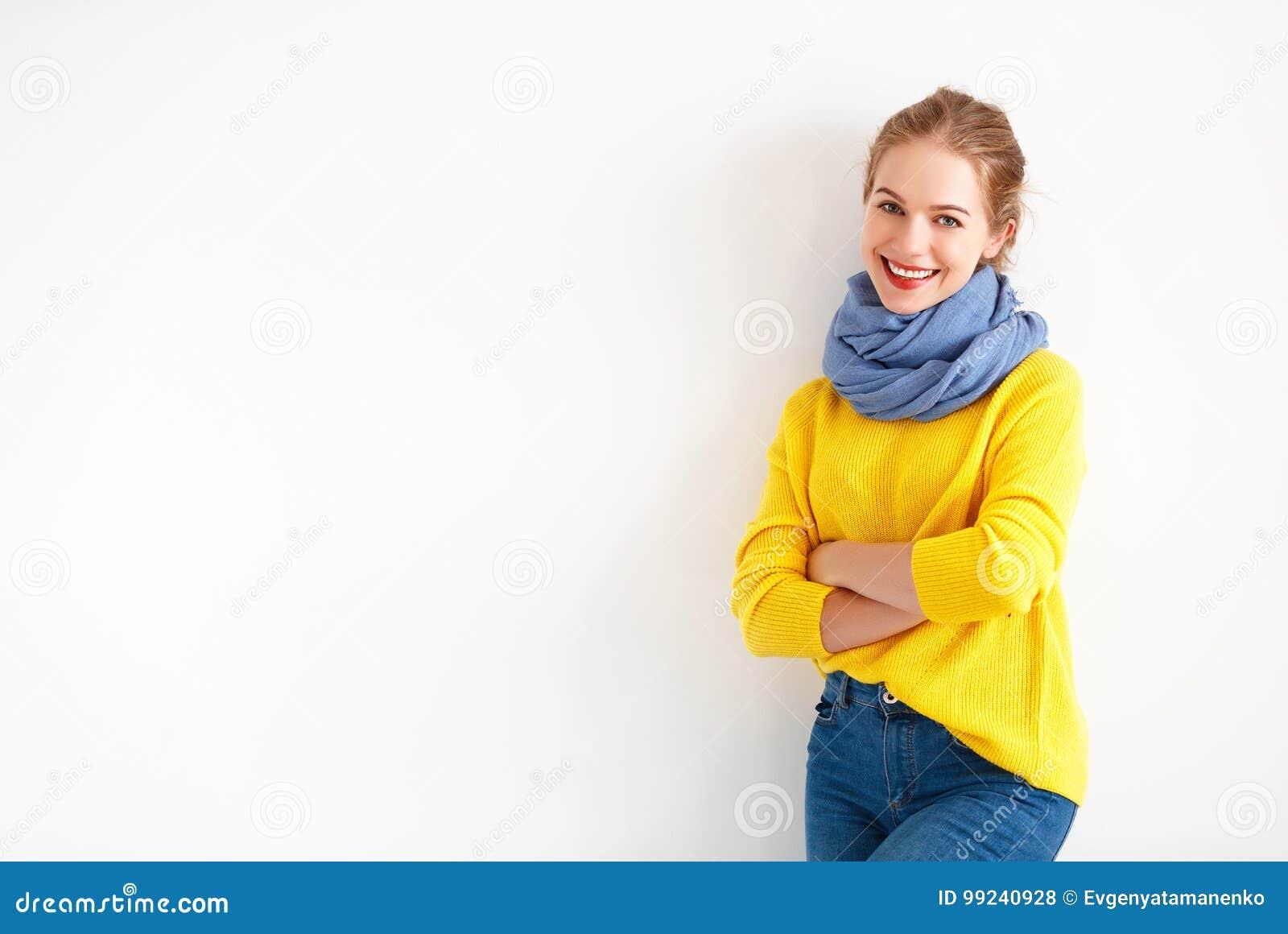 Glückliche junge Frau in der gelben Strickjacke auf weißem Hintergrund