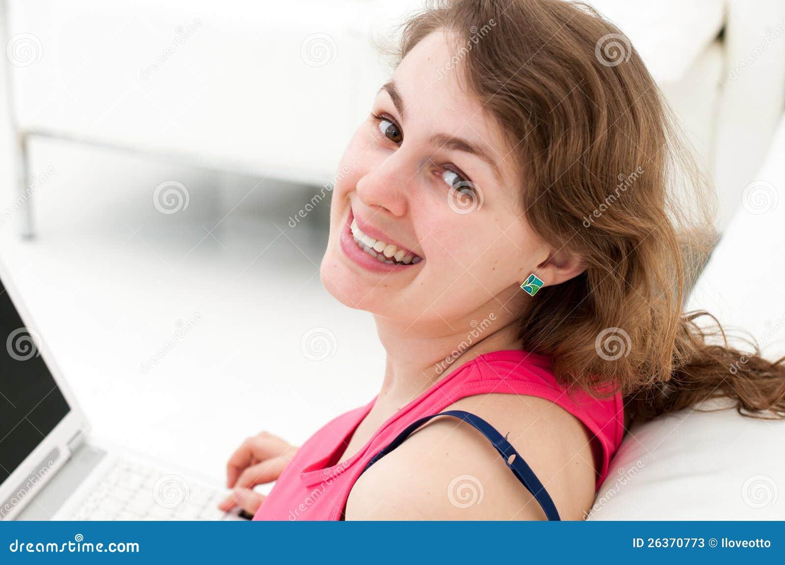 Glückliche junge Frau, die auf Couch mit einem Laptop sitzt