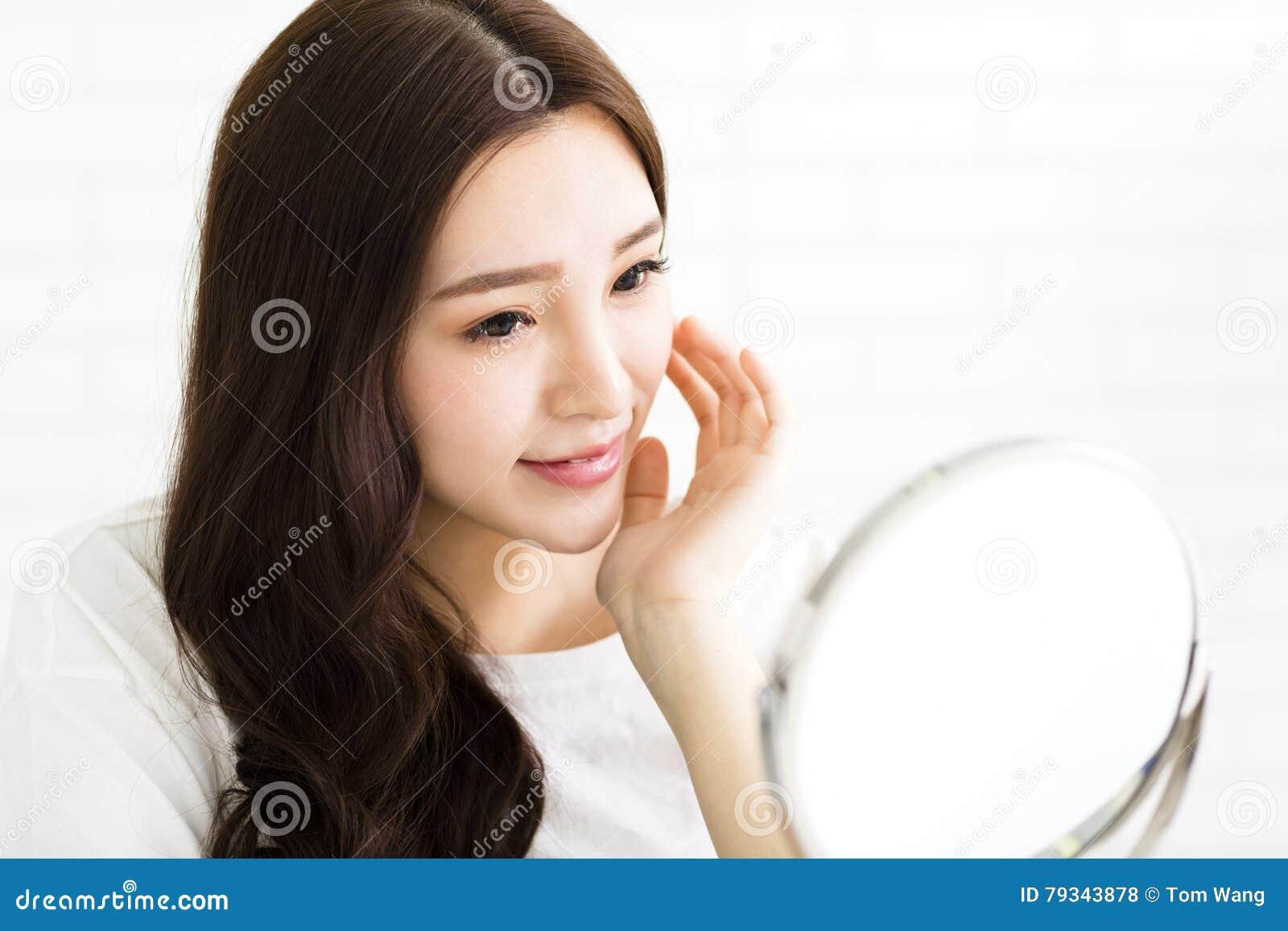 Glückliche junge Frau, die auf Spiegel schaut