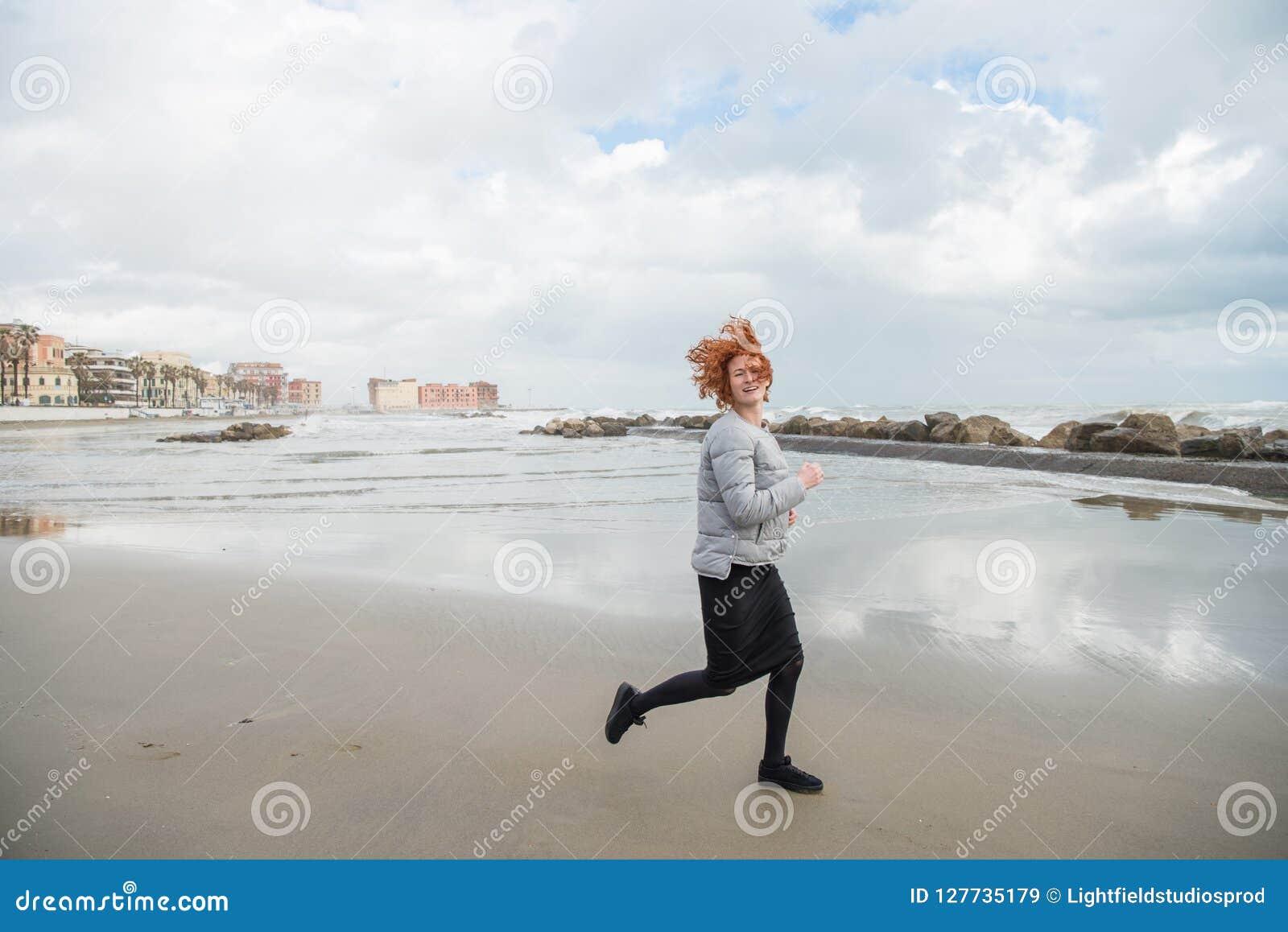 Glückliche junge Frau, die durch Küste am bewölkten Tag läuft