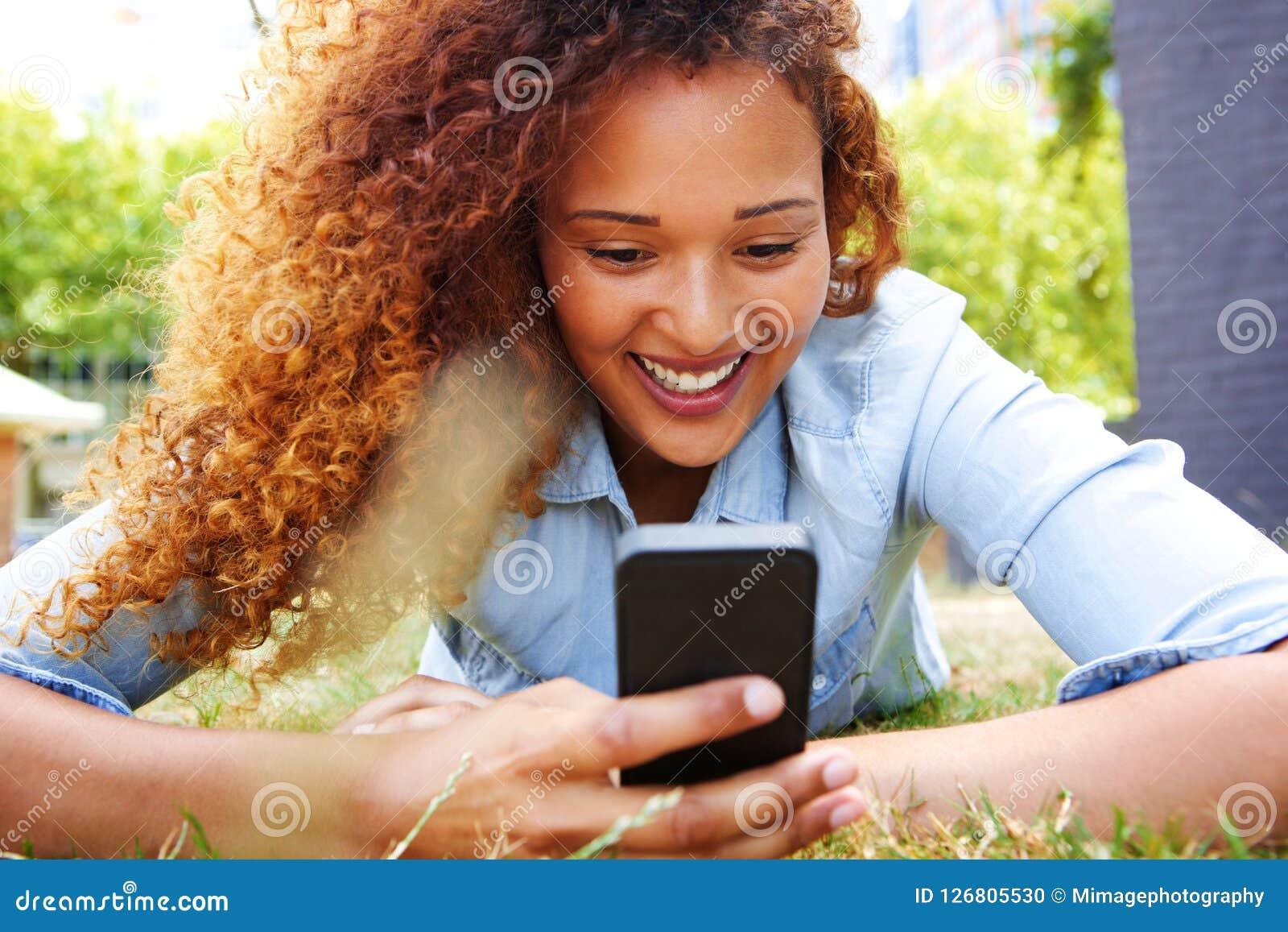 Glückliche junge Frau, die im Gras liegt und Handy betrachtet
