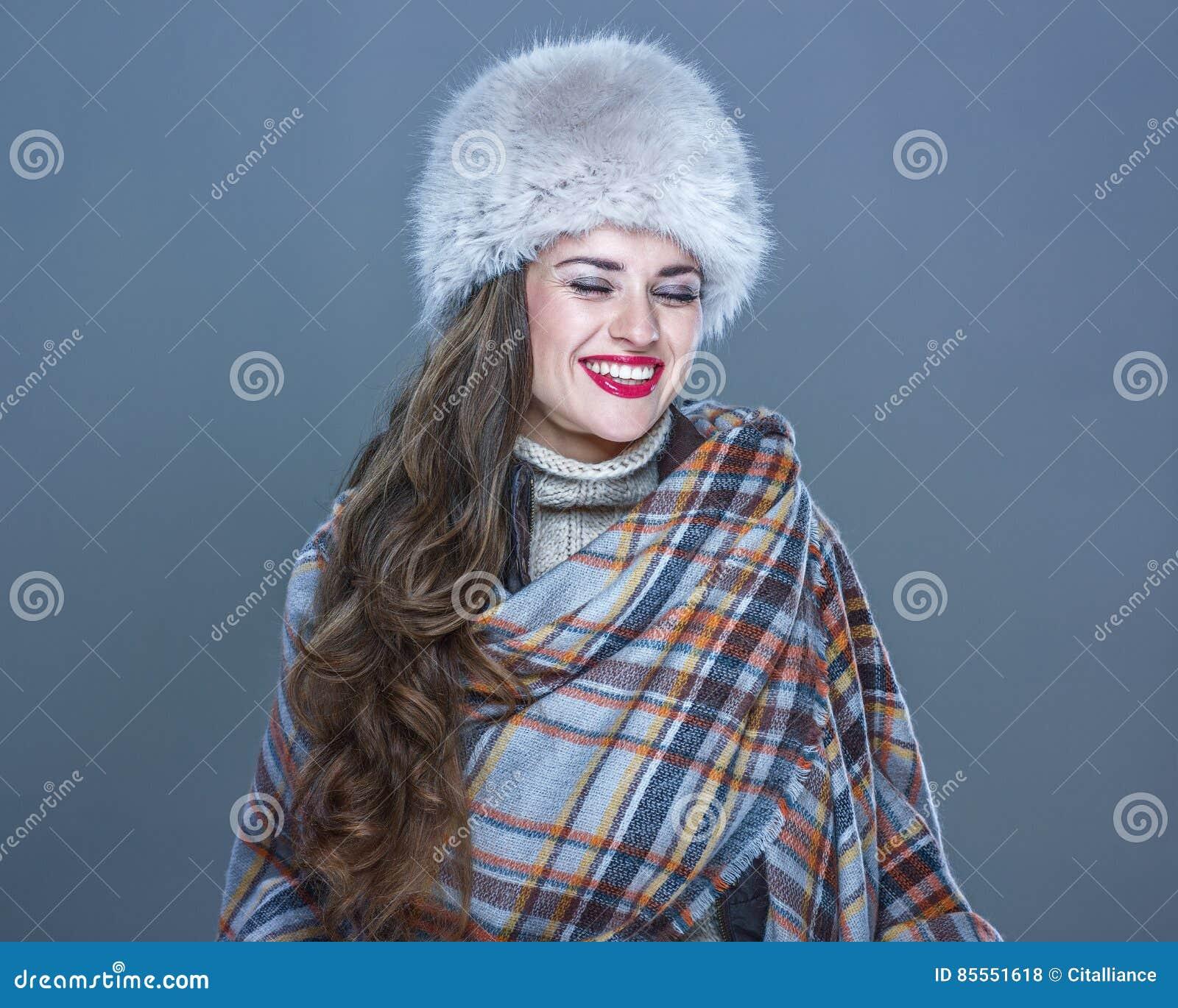 Glückliche junge Frau im Pelzhut lokalisiert auf dem kalten blauen Lachen