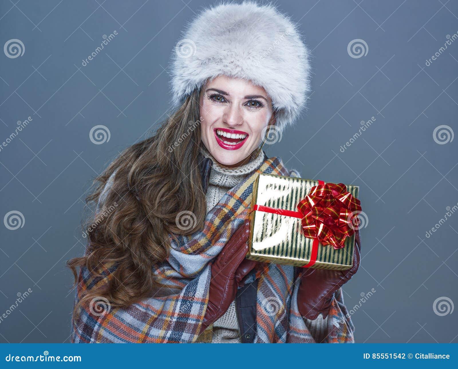 Glückliche junge Frau lokalisiert auf kaltem blauem darstellendem Präsentkarton