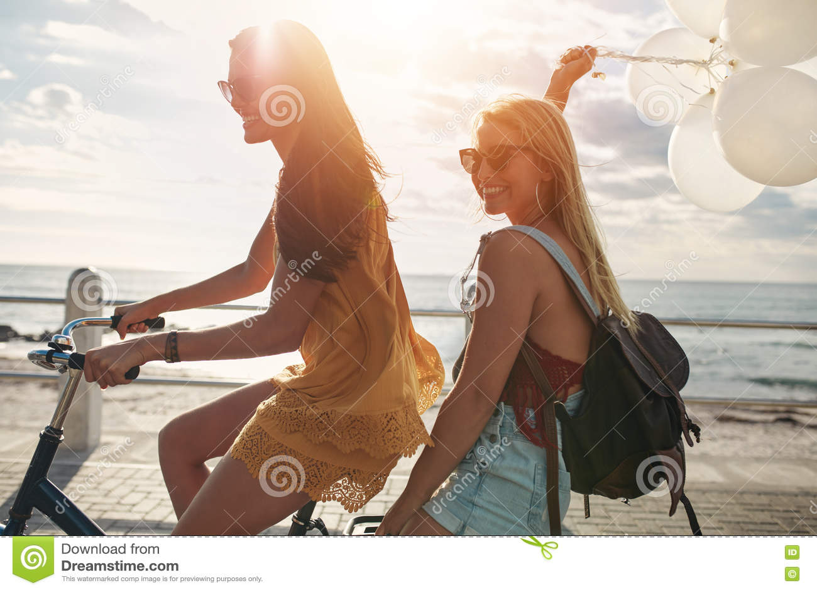 Glückliche junge Frauen auf Fahrrad zusammen mit Ballonen