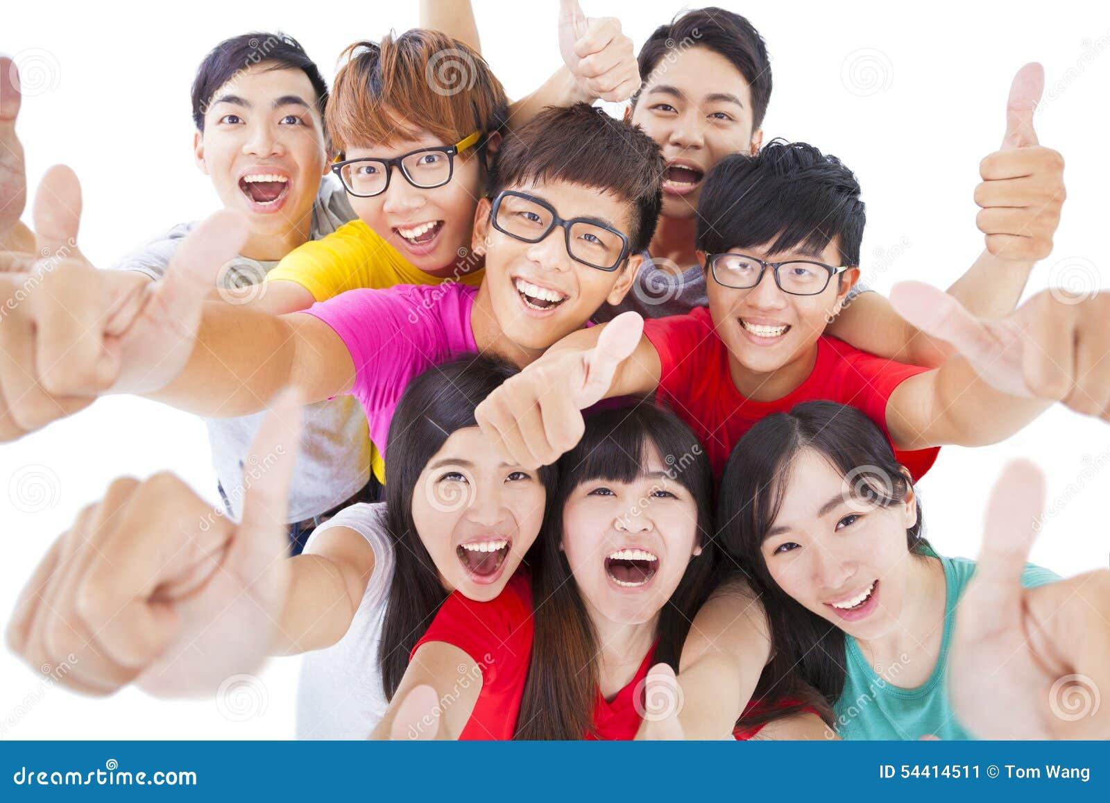Glückliche junge Gruppe mit den Daumen oben