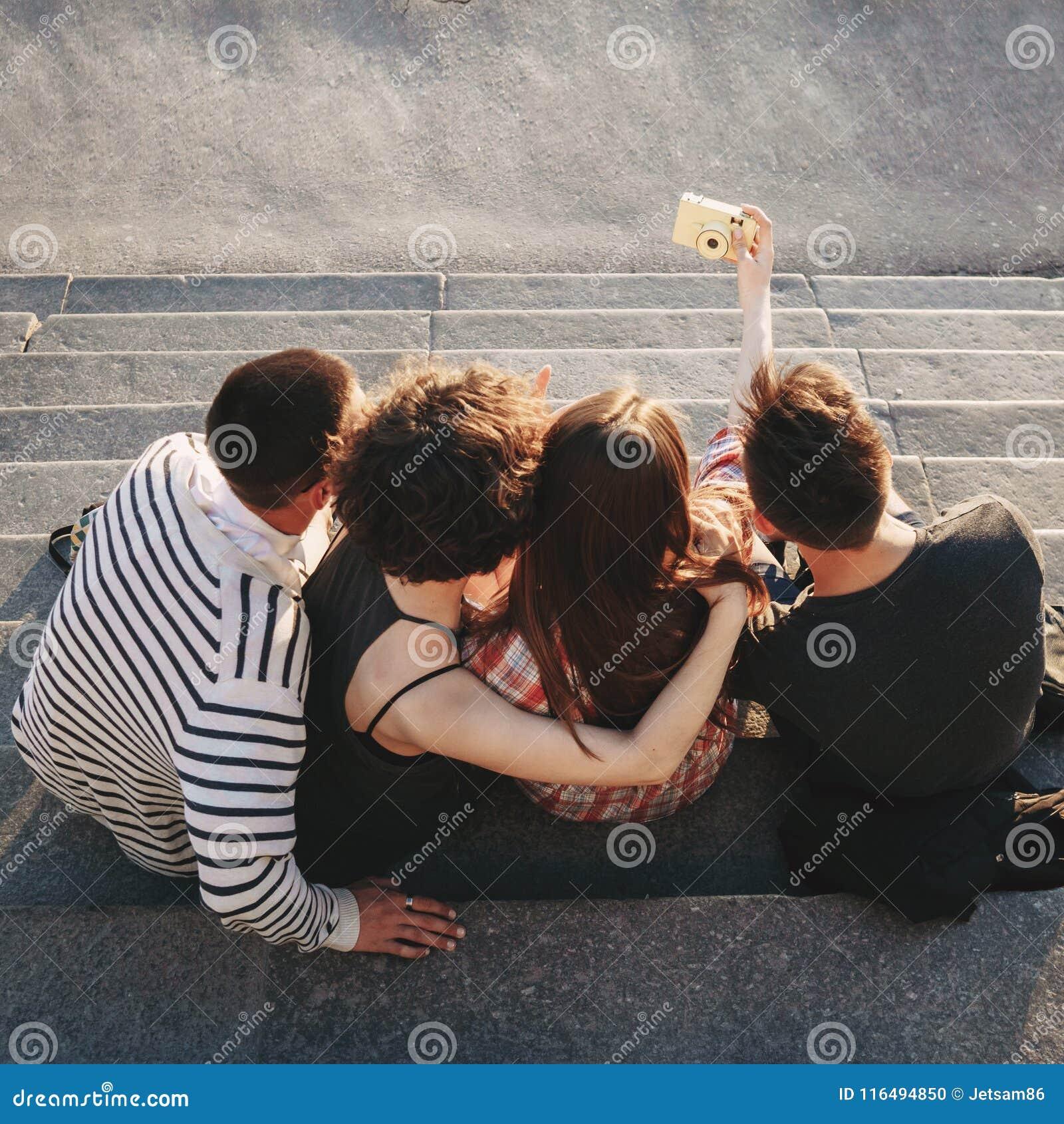 Glückliche junge Leute, die selfie an der Kamera in der Stadt nehmen