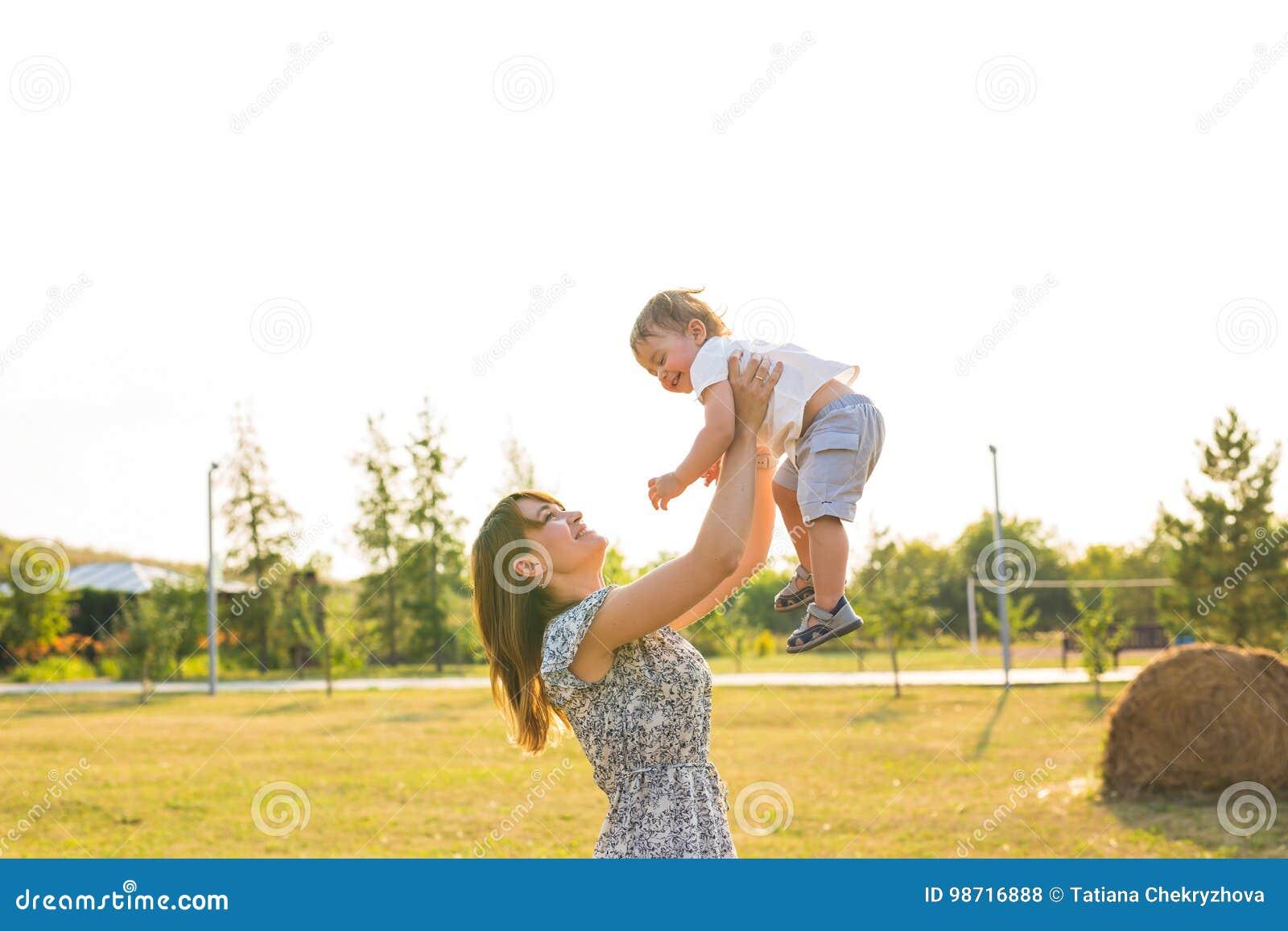 Glückliche junge Mutter, die mit ihrem kleinen Babysohn am warmen Herbst des Sonnenscheins oder am Sommertag spielt Schönes Sonne