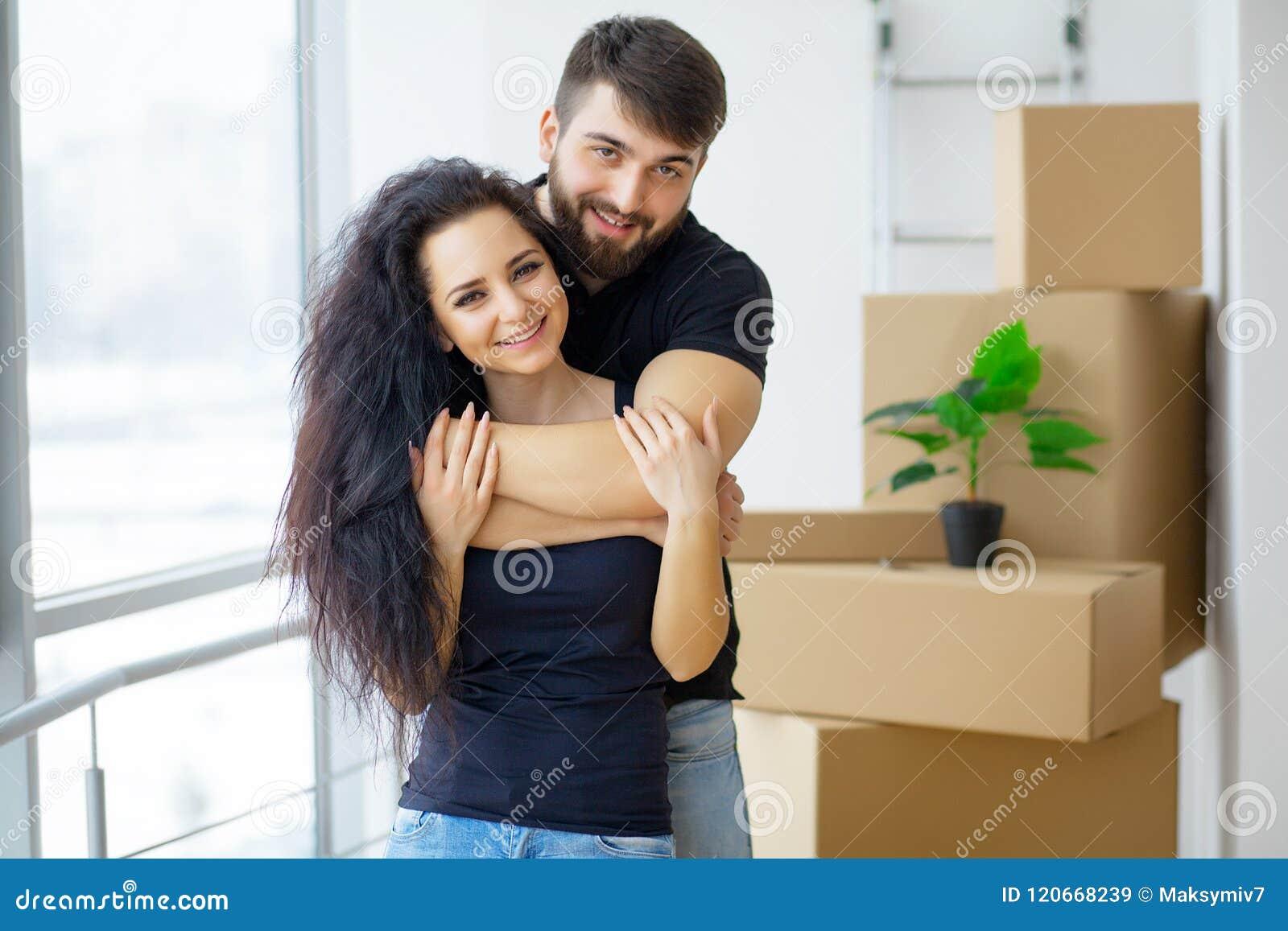 Glückliche junge Paare, die in das neue Haus auspackt Kästen sich bewegen