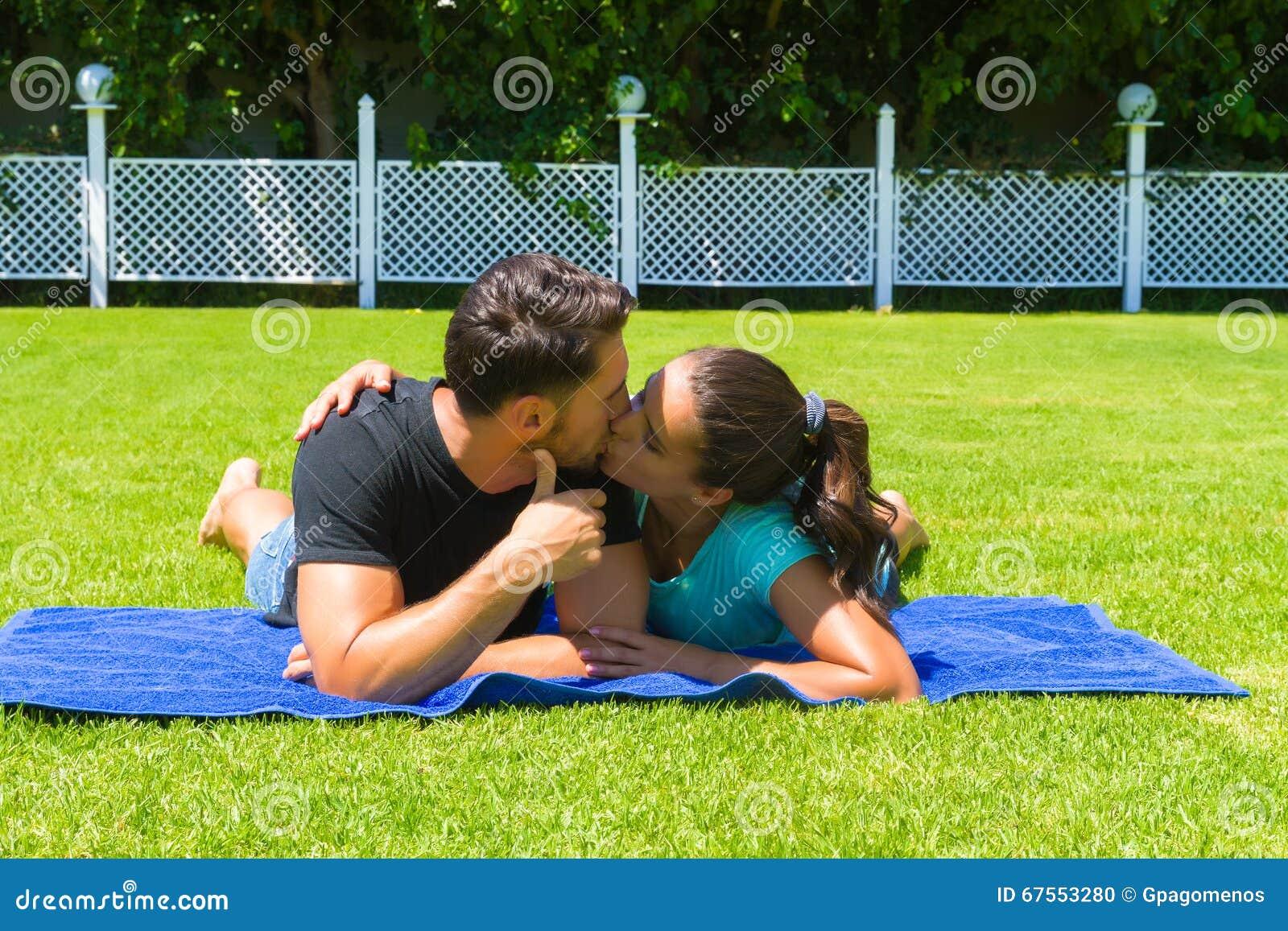 Glückliche junge Paare, die die Sonne genießend sich entspannen