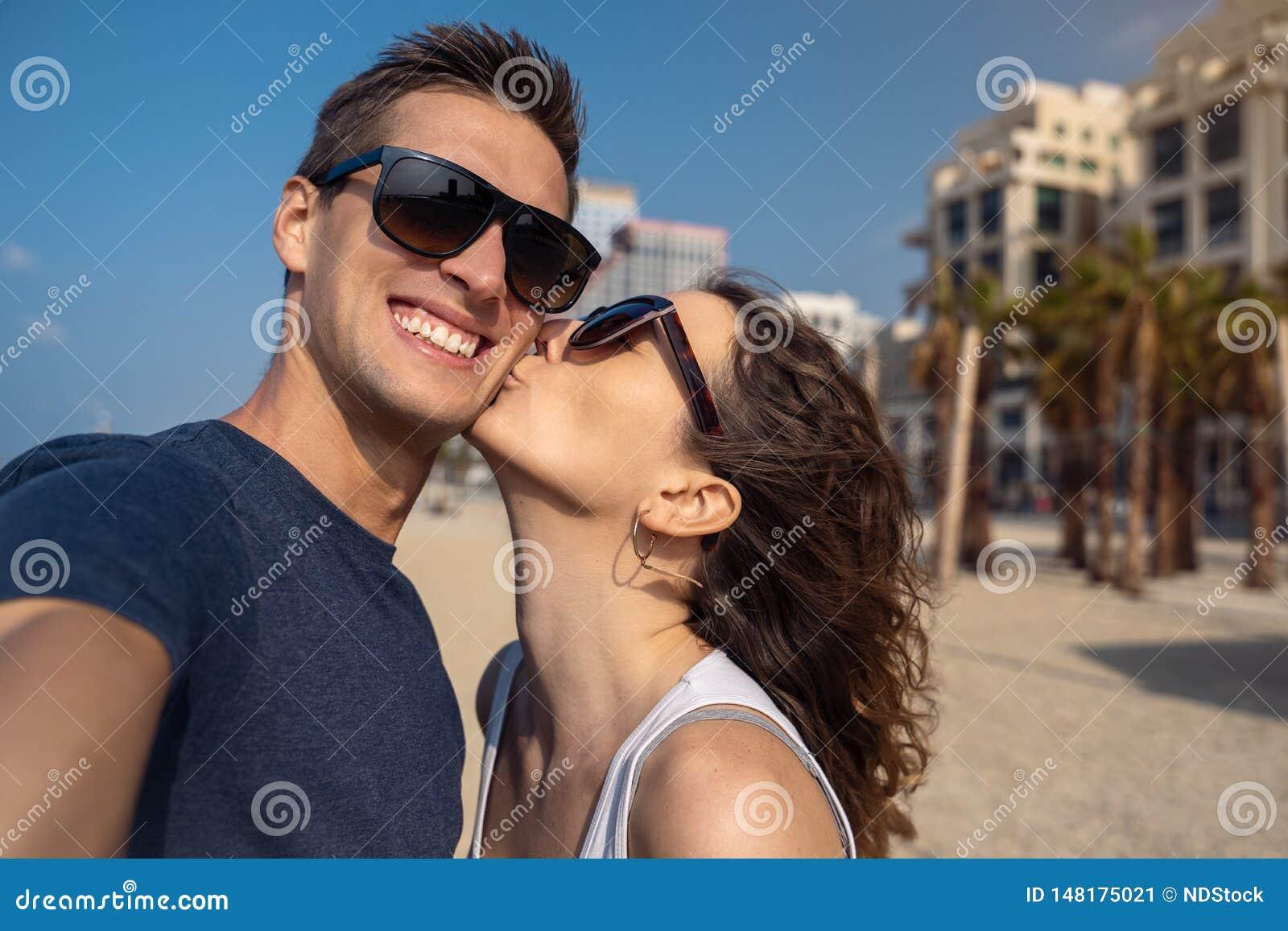 Glückliche junge Paare, die ein selfie auf dem Strand in Tel Aviv nehmen
