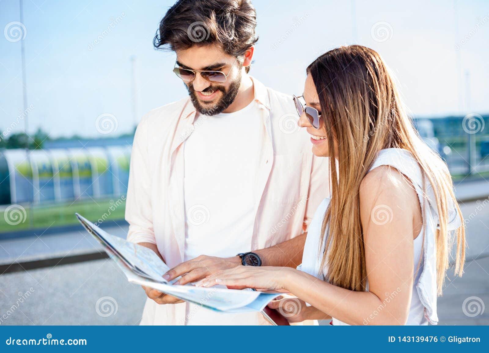 Glückliche junge Paare, die eine Karte betrachten und nach Richtungen suchen
