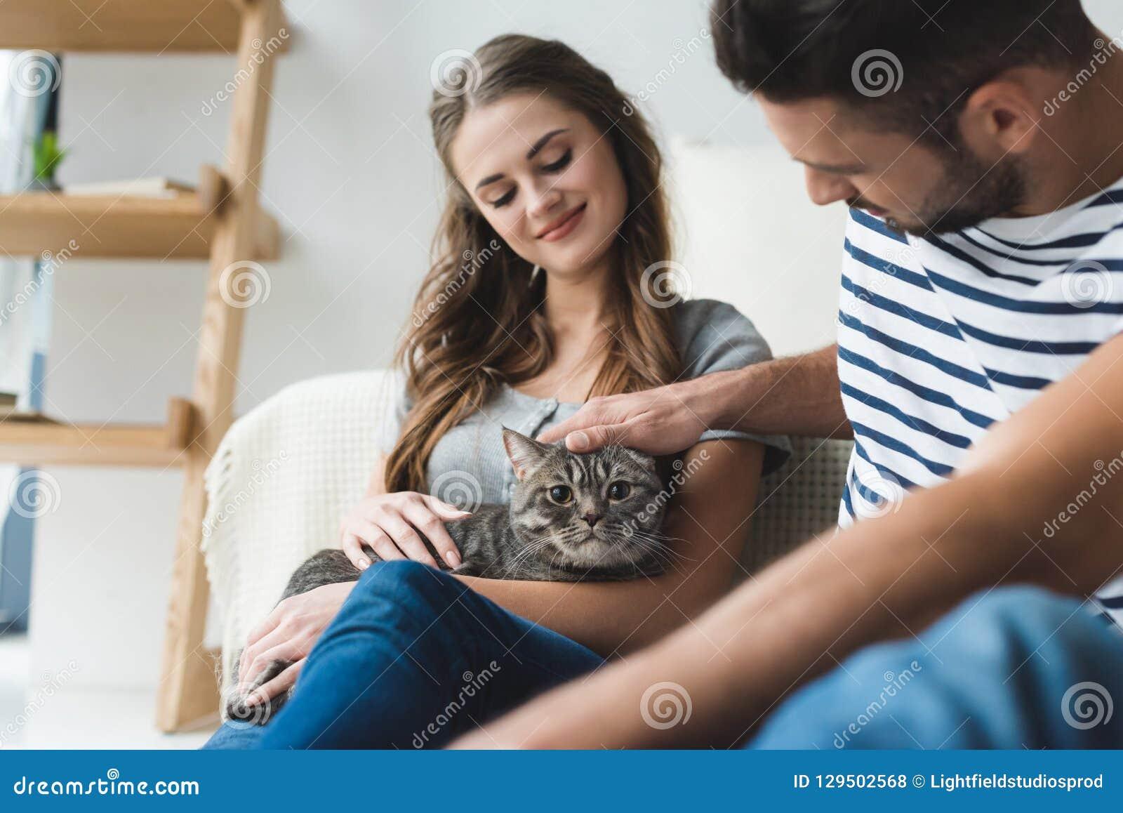 Glückliche junge Paare, die zu Hause Katze beim Sitzen streicheln