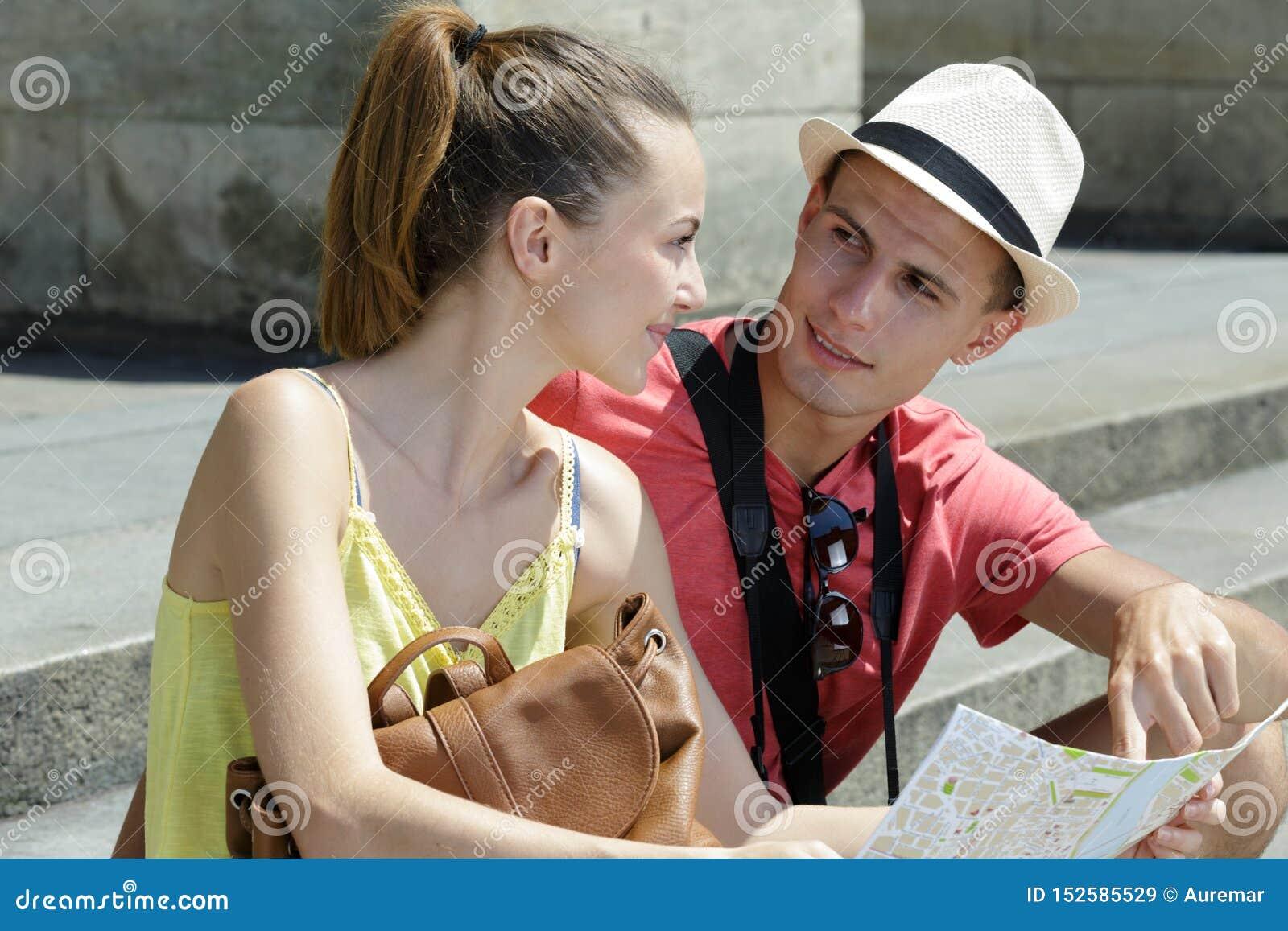 Glückliche junge Paare mit touristischer Kartenstadt