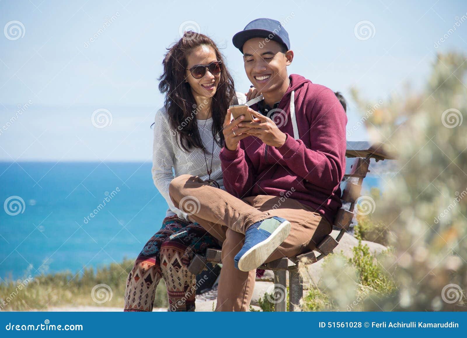 Glückliche junge Paare zusammen unter Verwendung des Handys