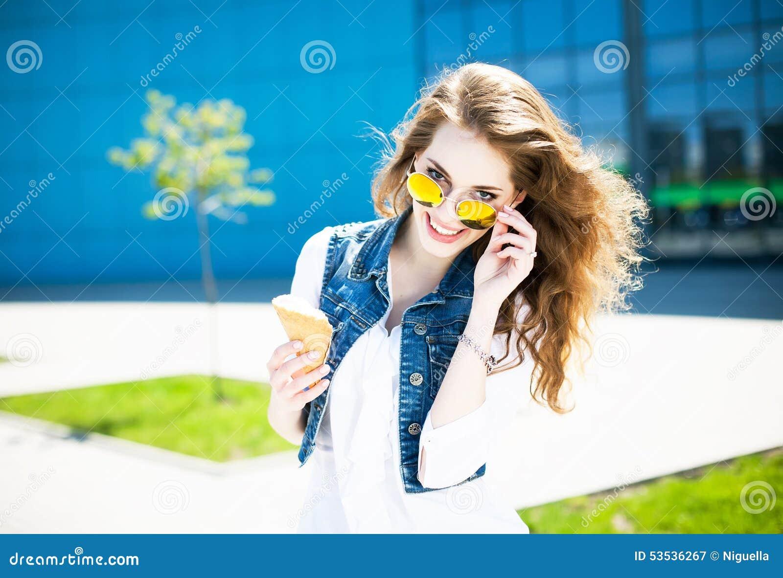 Glückliche junge Schönheit mit dem gelockten Haar und den stilvollen sunglass