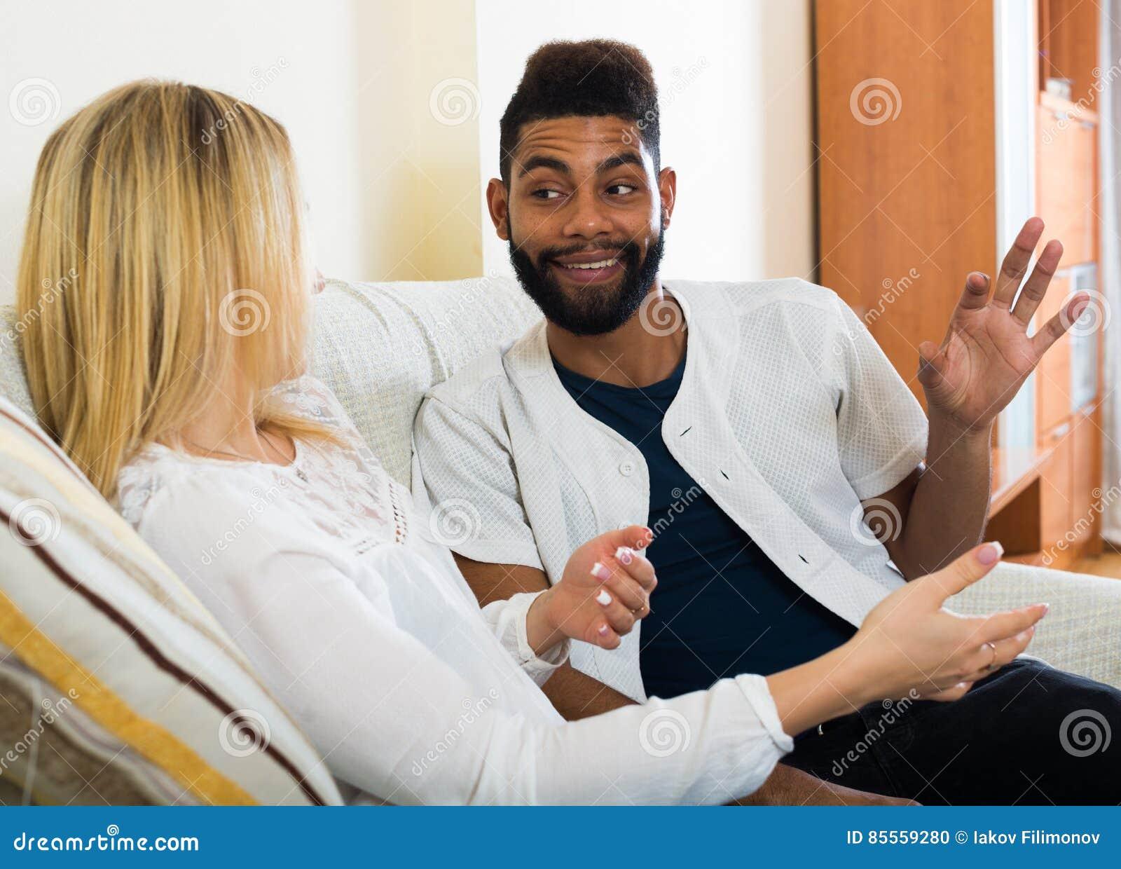 Glückliche junge zuhause sitzende und sprechende Leute