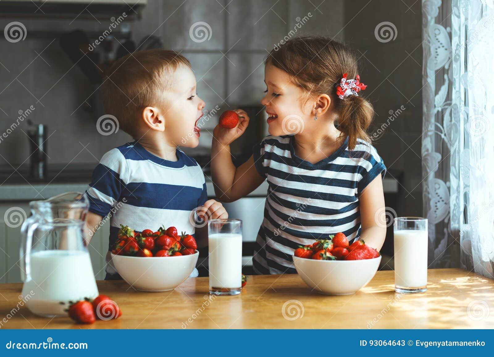 Glückliche Kinder Bruder und Schwester, die Erdbeeren mit Milch essen