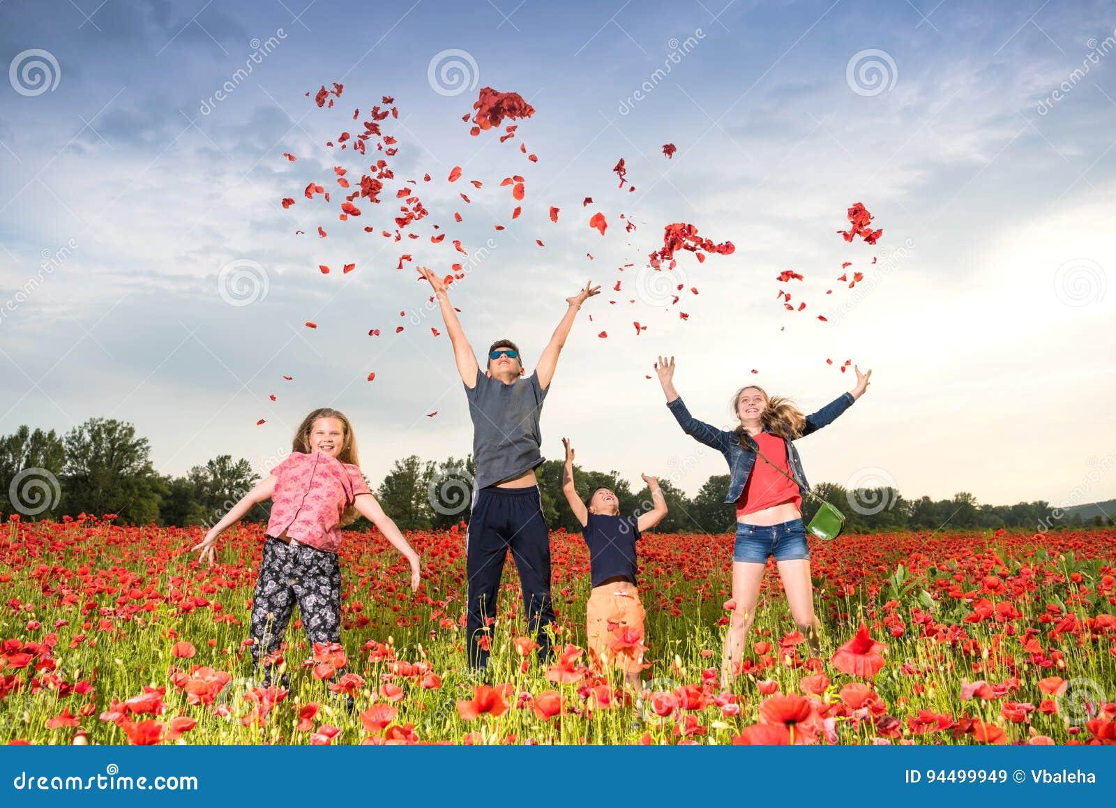 Glückliche Kinder, die Blumenblätter von Mohnblumen springen und werfen