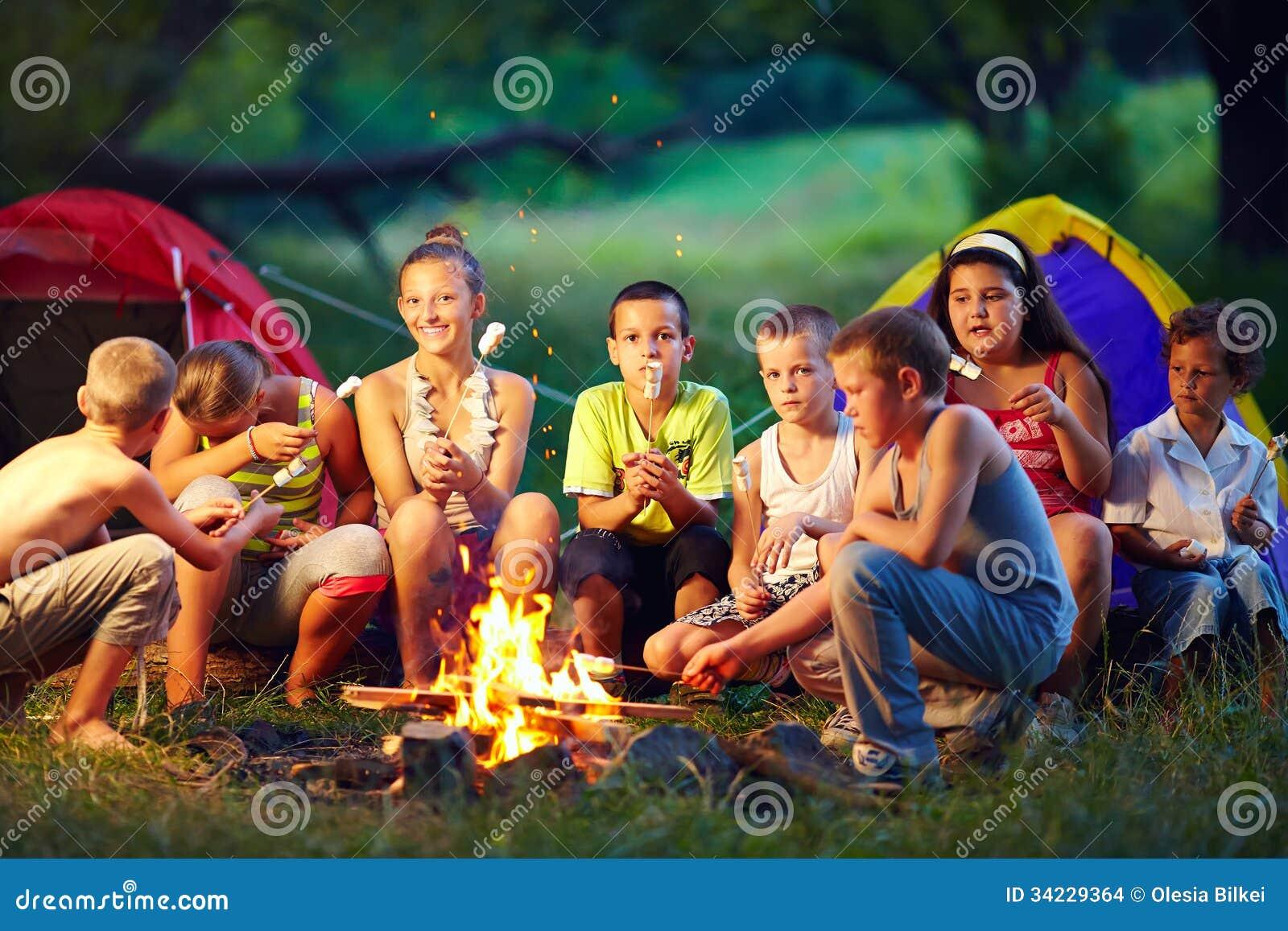 Glückliche Kinder, die Eibische auf Lagerfeuer braten