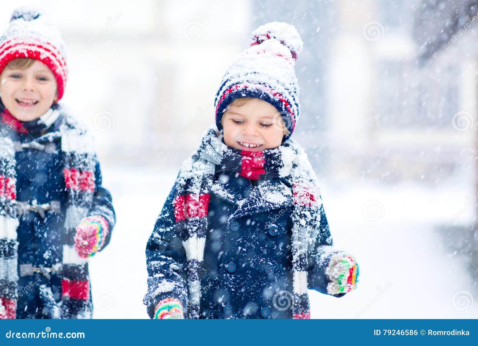 Glückliche Kinder, die Spaß mit Schnee im Winter haben