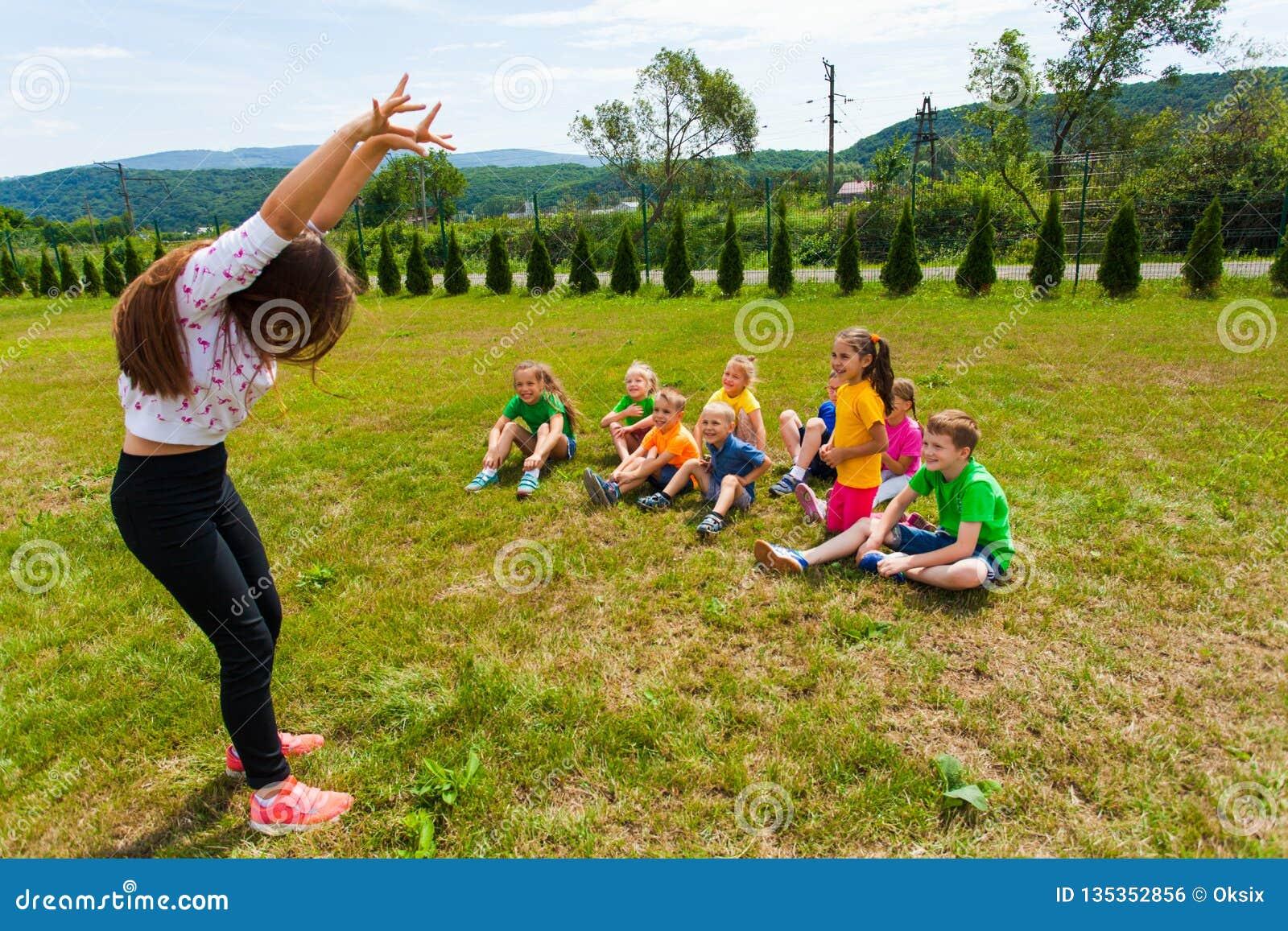 Glückliche Kinder, die während des Scharadespiels Sommerlager schätzen