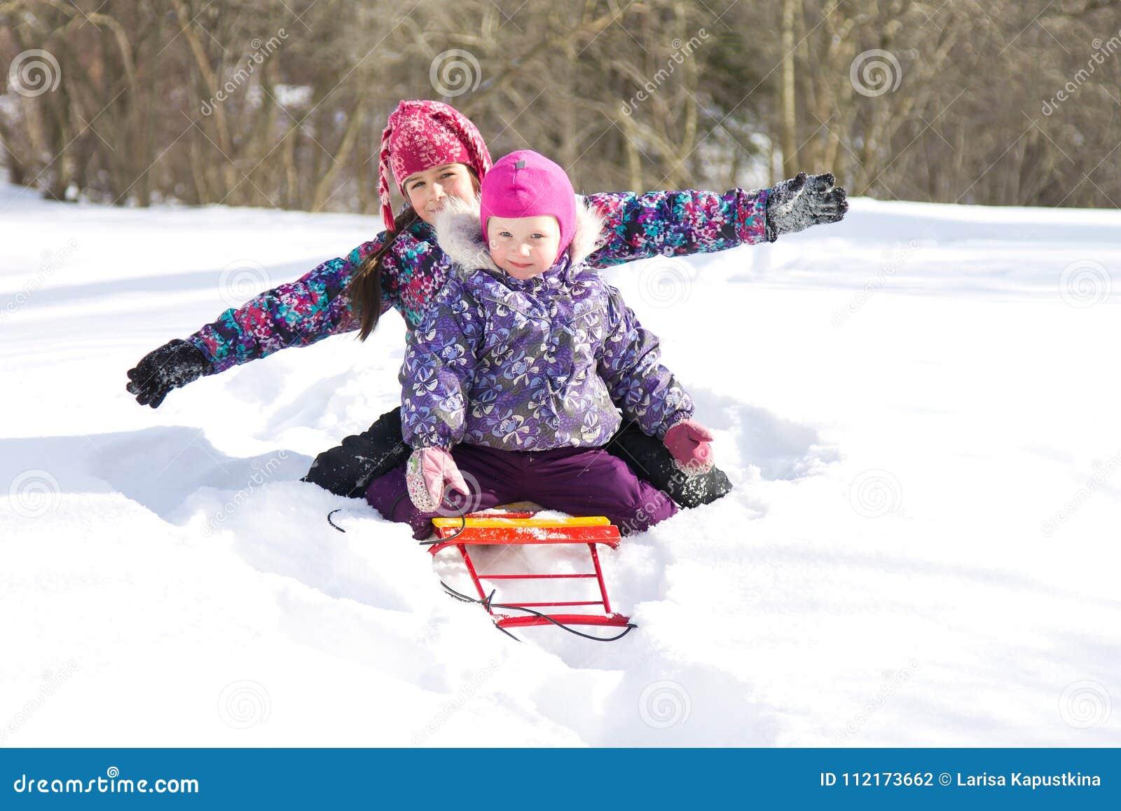 Glückliche Kinder, die zusammen auf einem Schlitten in einer Schneewehe an einem klaren Wintertag sitzen