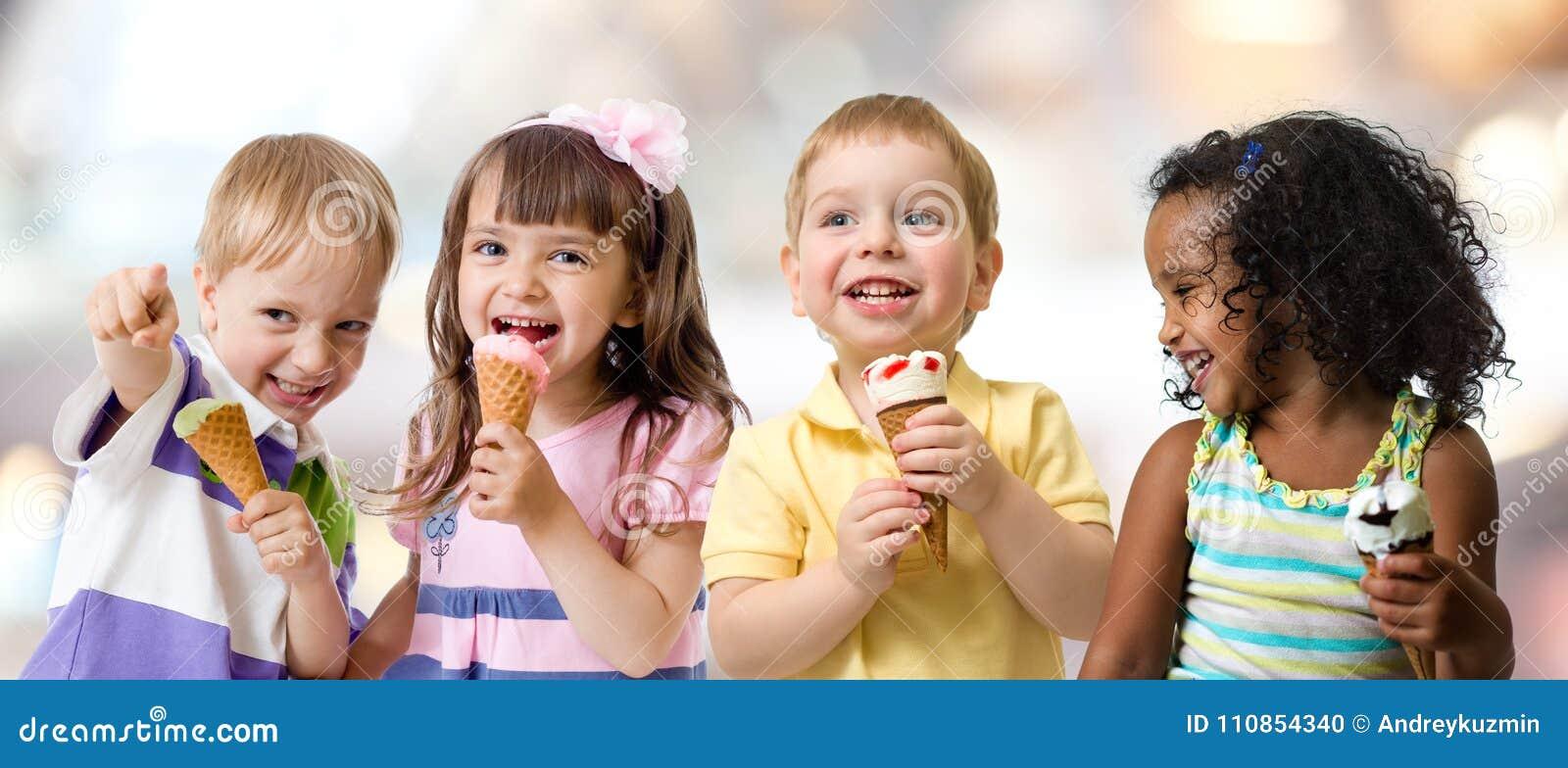 Glückliche Kinder gruppieren das Essen der Eiscreme an einer Partei im Café