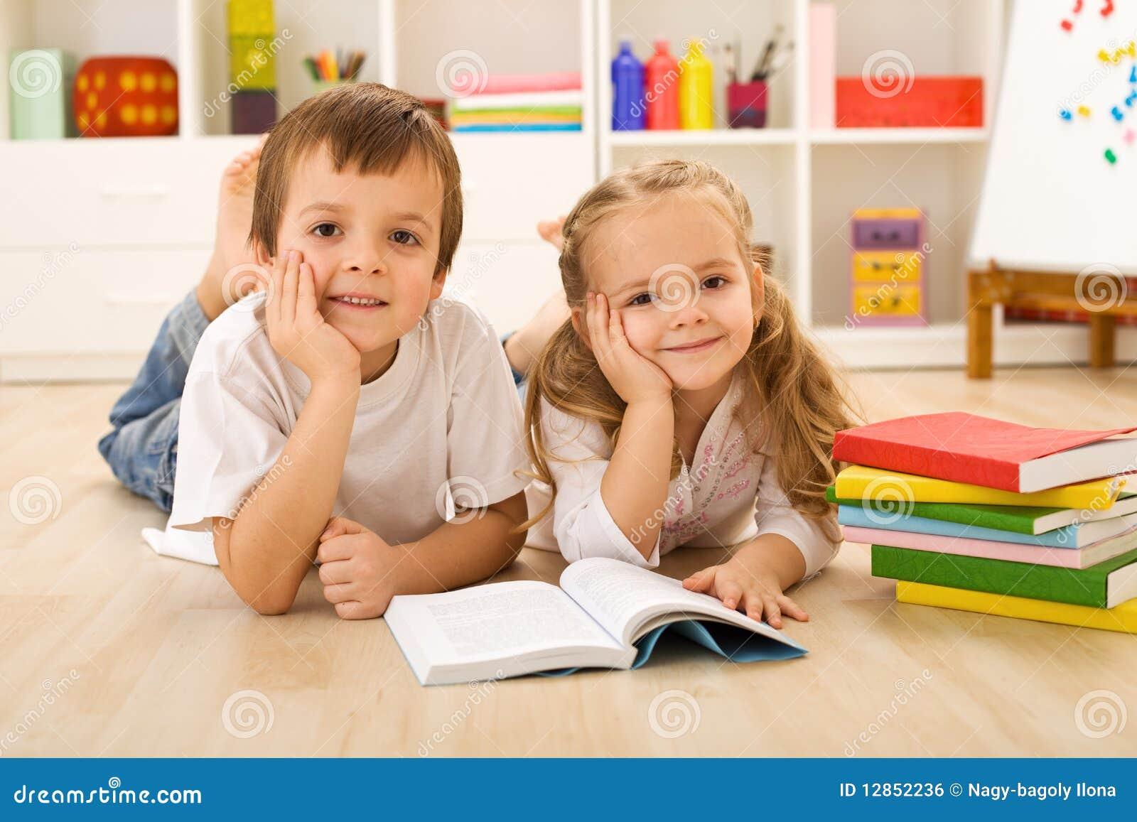 Glückliche Kinder mit den Büchern, die auf den Fußboden legen