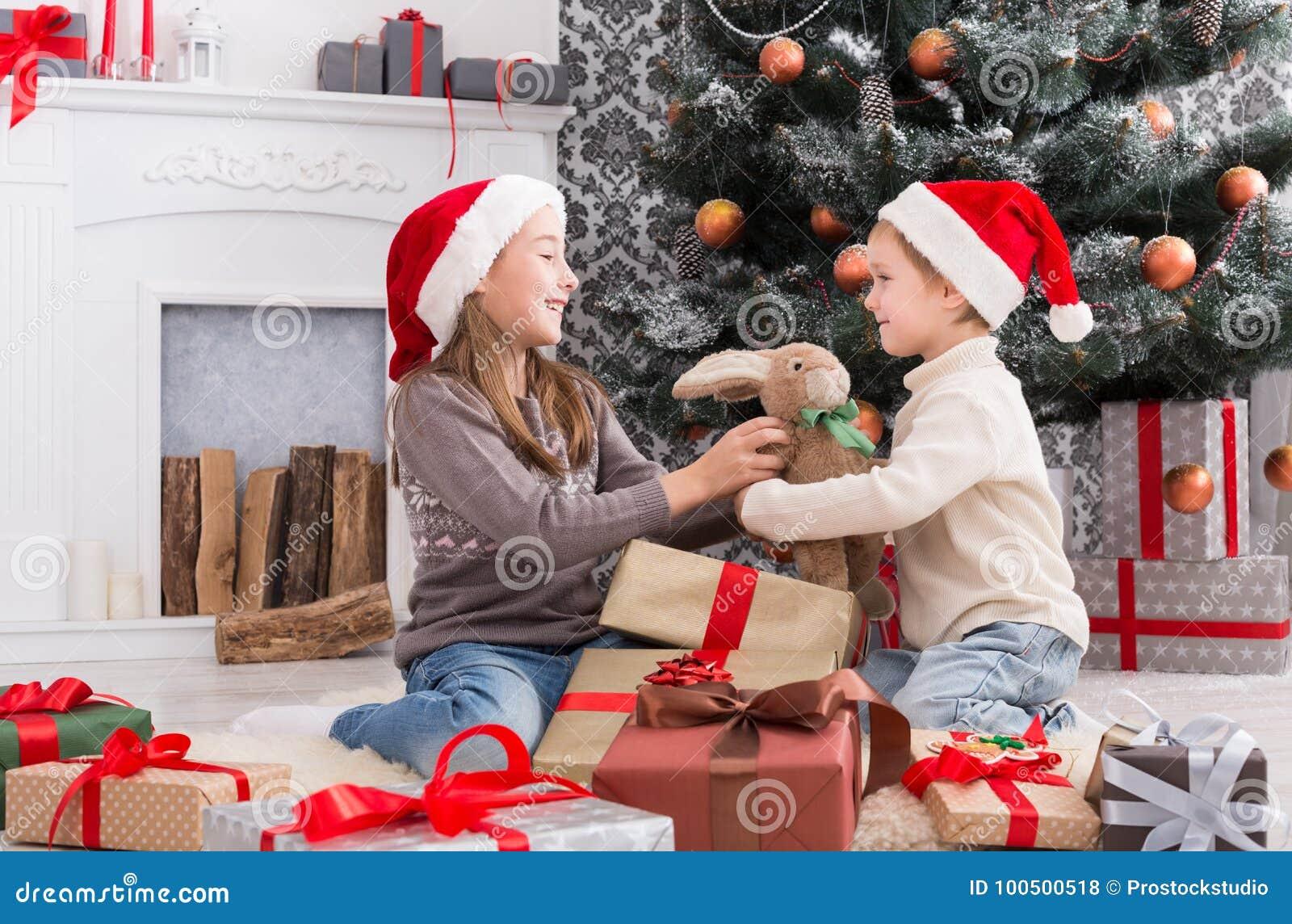Die Weihnachtsgeschenke.Glückliche Kinder In Sankt Hüten Die Weihnachtsgeschenke Auspacken