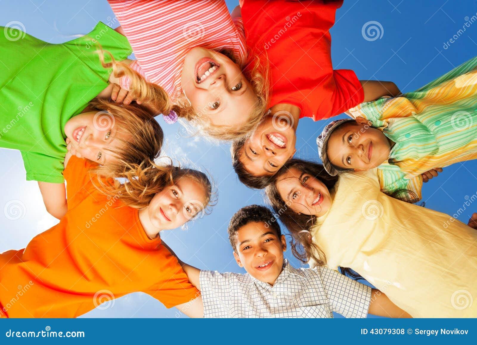 Glückliche Kinder schließen im Kreis auf Himmelhintergrund