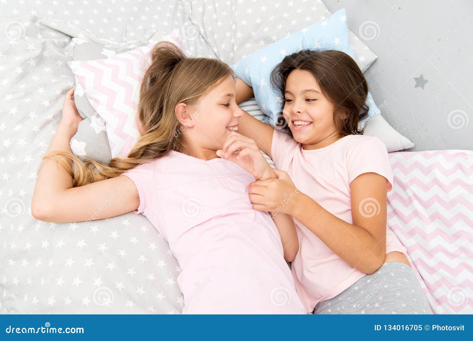 Glückliche kleine Kinder der Schwestern, die im Schlafzimmer sich entspannen Freundschaft von kleinen Mädchen Freizeit und Spaß S