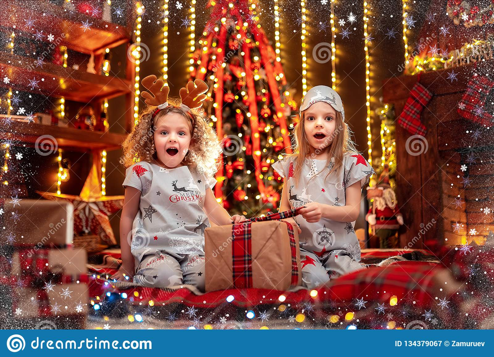 Glückliche kleine Mädchen, die offene Geschenkbox der Weihnachtspyjamas durch einen Kamin in einem gemütlichen dunklen Wohnzimmer