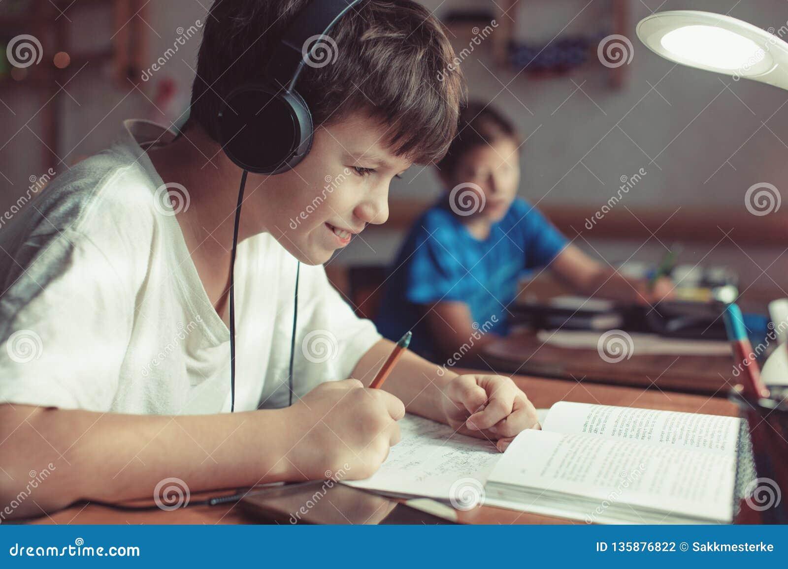 Glückliche kleine Schüler, die zu Hause Hausarbeit tun